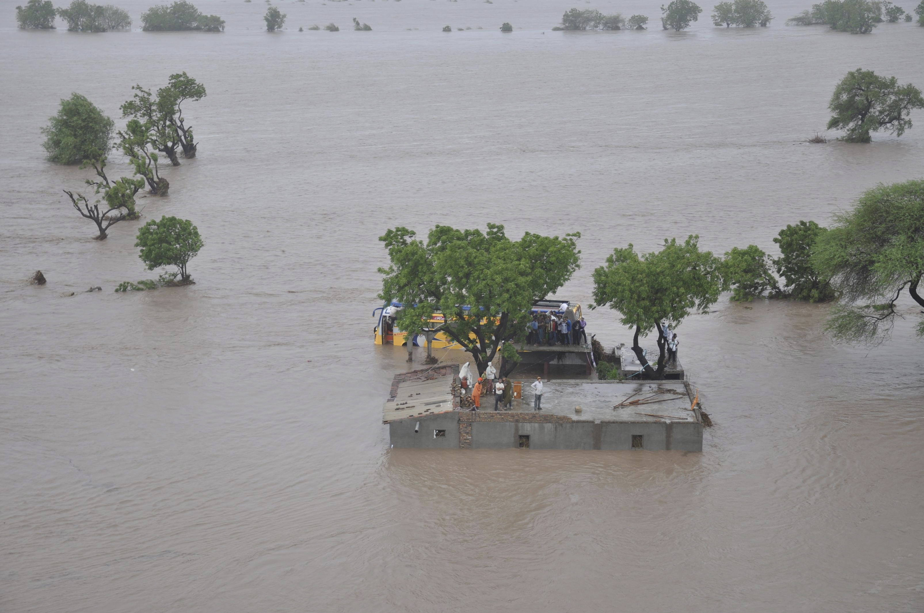 An aerial view shows flood victims standing atop their submerged houses in Amreli district of Gujarat, India, in this June 24, 2015 handout provided by the Indian Air Force.