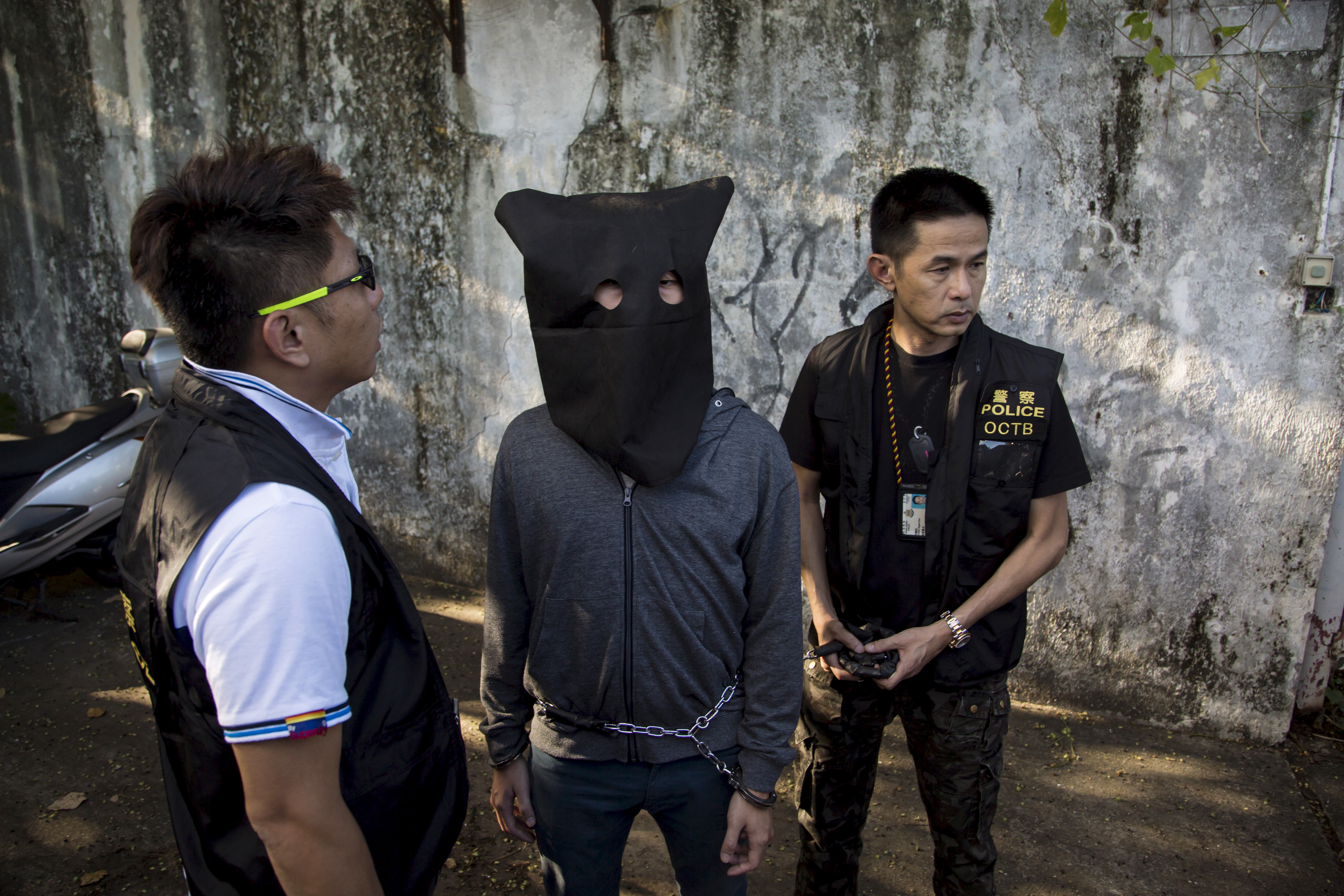 Police officers stand around a man, suspected of a bomb-making plot ahead of an electoral reform vote, as he is brought to an abandoned former Asia Television Limited (ATV) studio for investigation in Hong Kong, China June 16, 2015