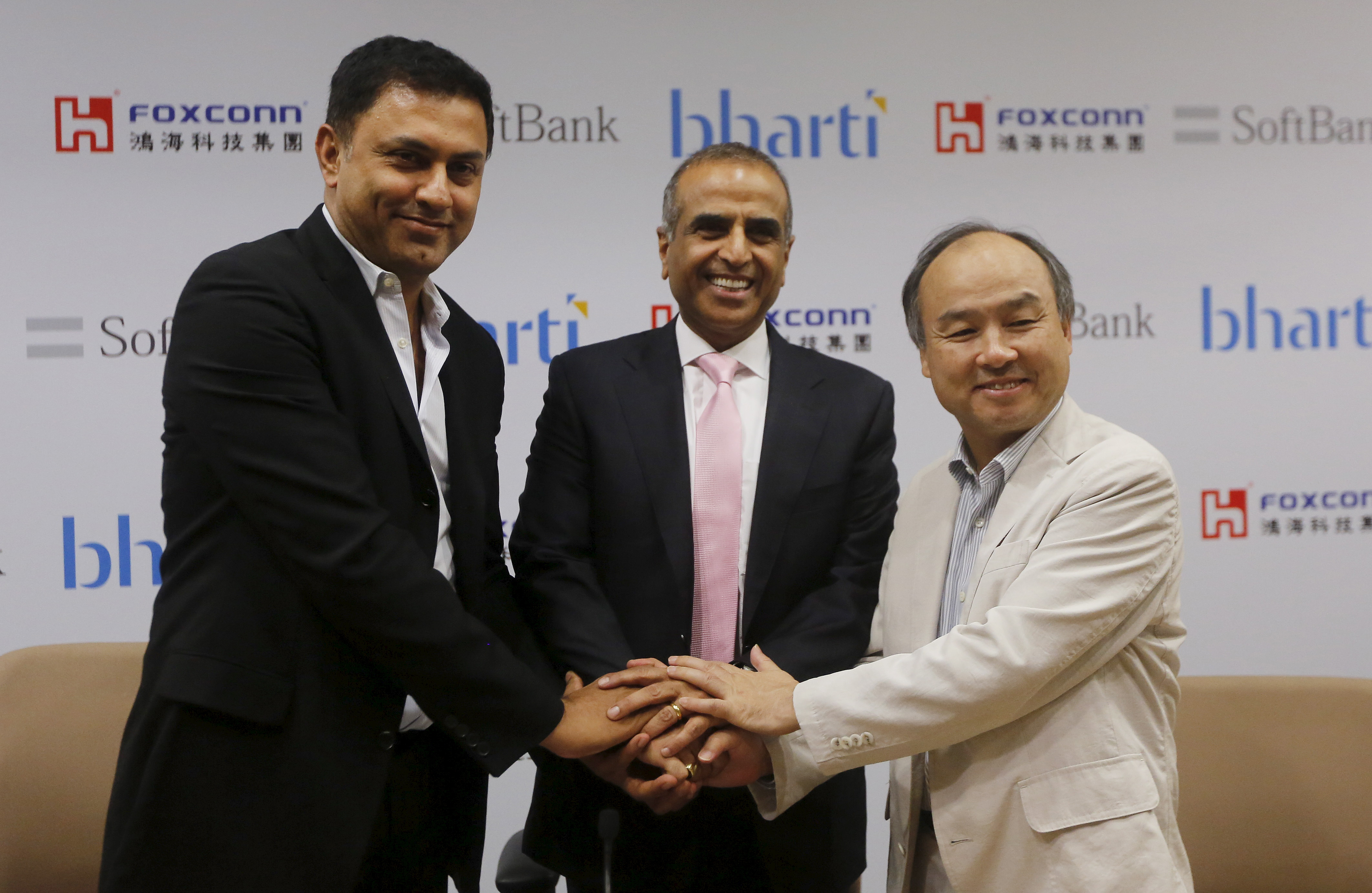 From right: Masayoshi Son, right, founder and CEO of SoftBank; Sunil Bharti Mittal, chairman of Bharti Enterprises; and Nikesh Arora, president of SoftBank, shake hands before the start of a news conference in New Delhi on June 22, 2015