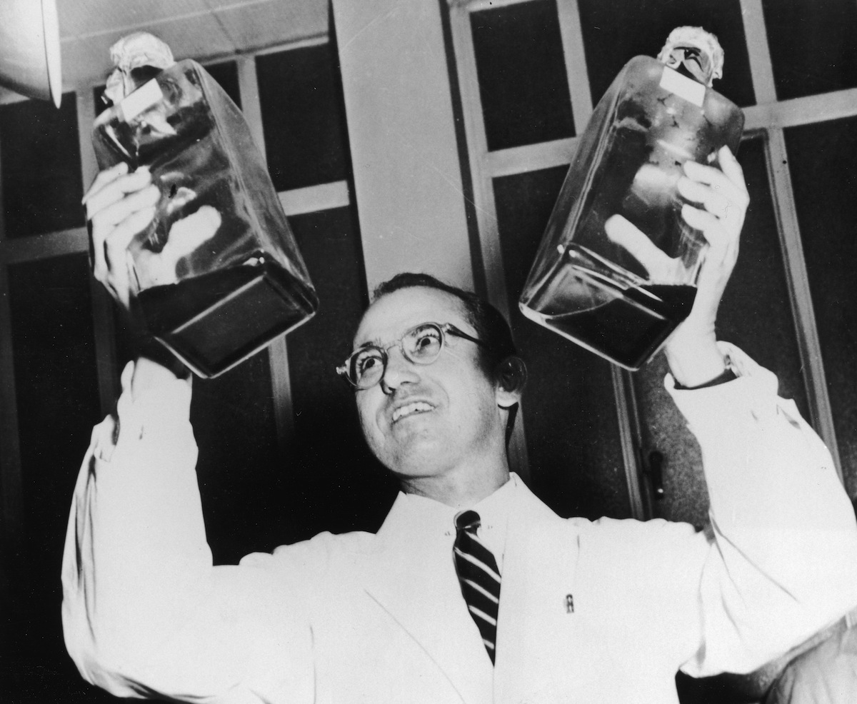 Jonas Salk (1914 - 1995) holding up two decanters containing the anti-polio vaccine that he developed.
