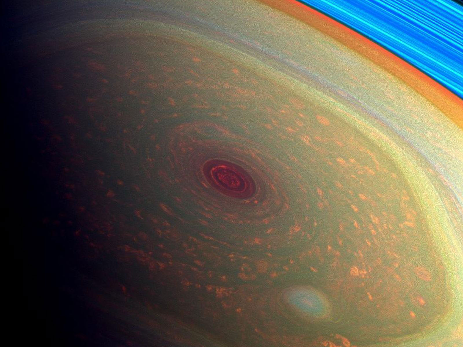 The Cassini spacecraft captured the storms at Saturn's north pole in this false color image released in April 2013. The storm appears dark red while the fast-moving hexagonal jet stream framing it is a yellowish green. Low-lying clouds circling inside the hexagonal feature appear in orange. A second, smaller vortex pops out in teal at the lower right of the image. The rings of Saturn appear in vivid blue at the top right.