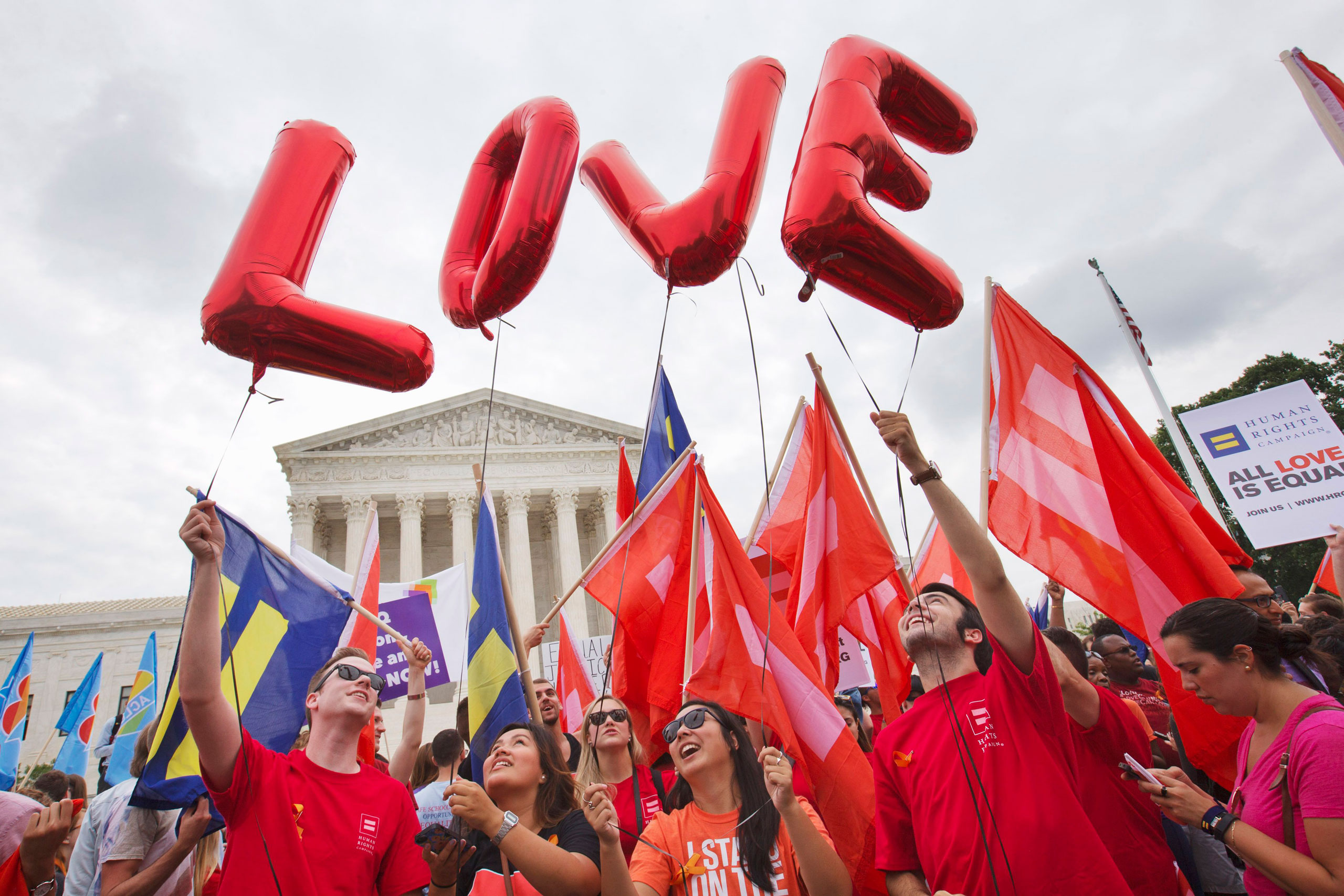 Same-sex marriage supporters hold up balloons that spell the word  love  as they wait outside of the Supreme Court in Washington, on June 26, 2015, before the court declared that same-sex couples have a right to marry anywhere in the US.