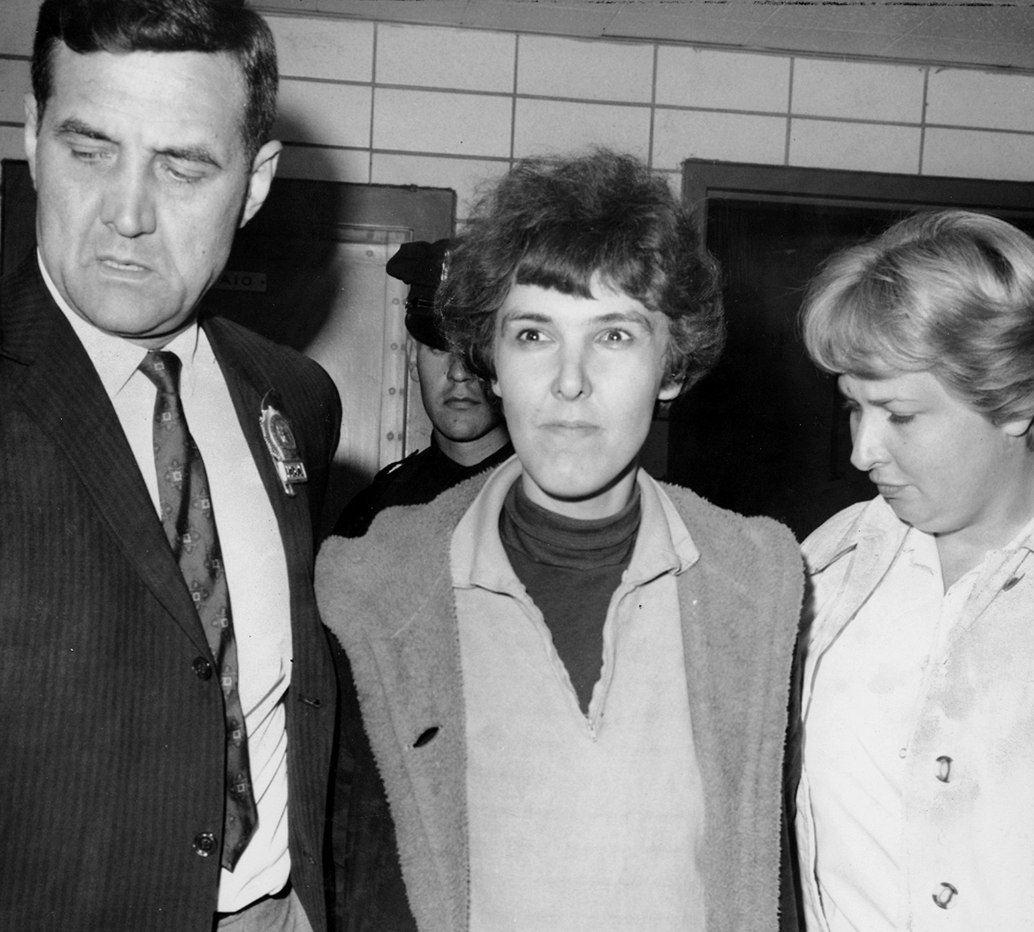 Detective Frederick Stepat and policewoman McCarthy escort Valeria Solanas, 28, into 13th precinct, for the shooting of Andy Warhol, on June 3, 1968, in New York City