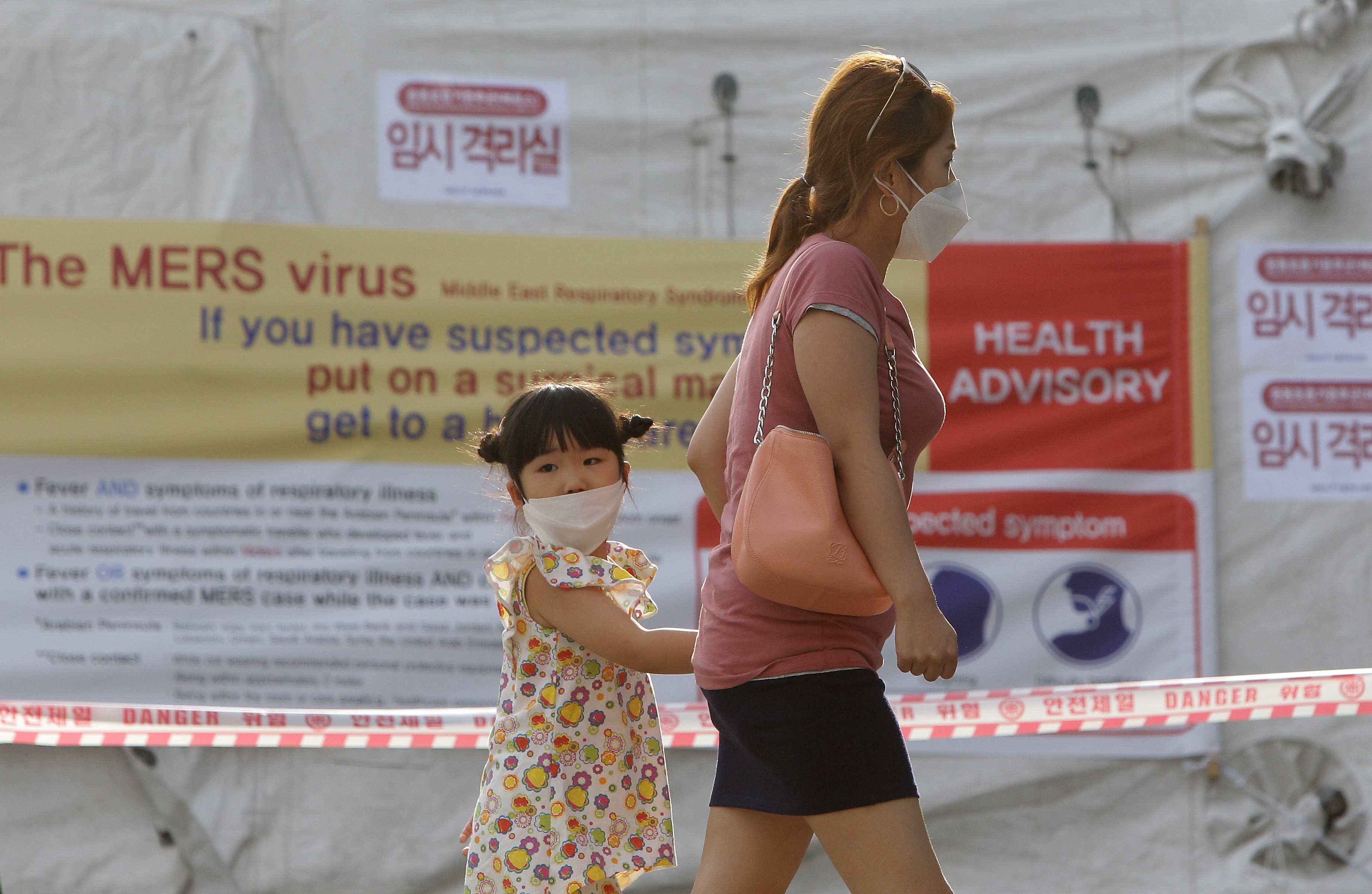 Visitors wearing masks walk in front of a health advisory sign about the MERS virus at a quarantine tent for people who could be infected with the MERS virus at Seoul National University Hospital on June 2 in Seoul, South Korea.