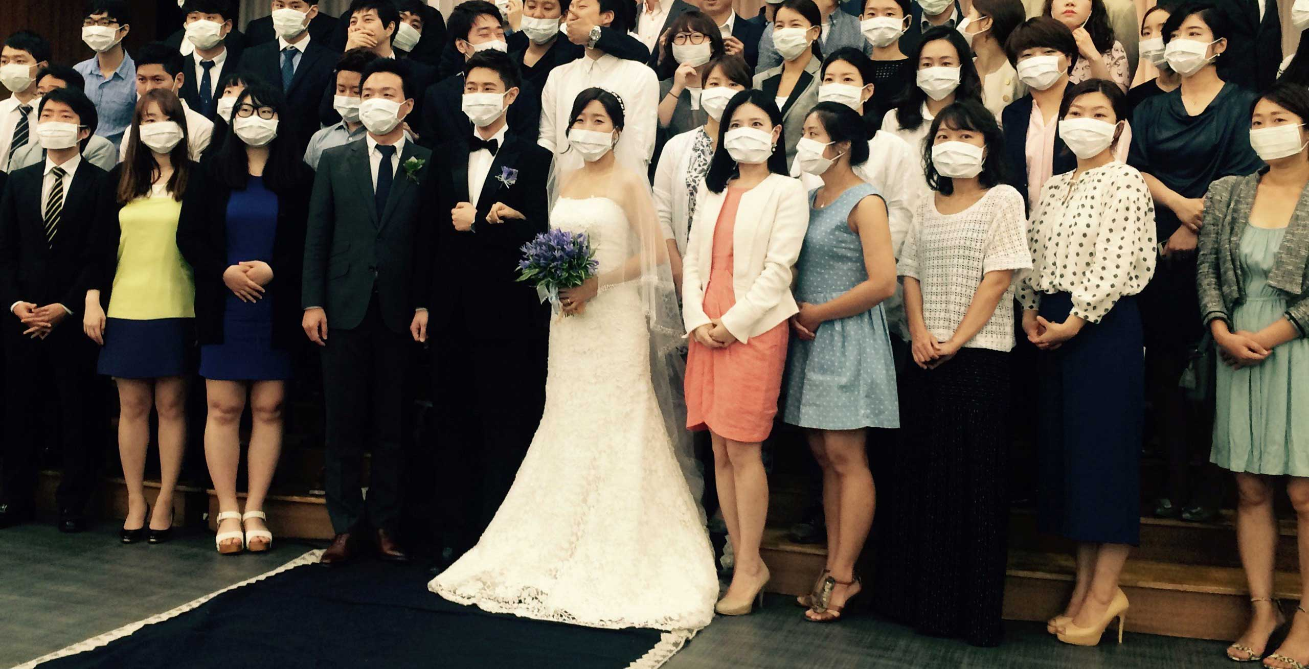 A young South Korean couple and dozens of guests standing together for a group photo in Seoul on June 6, 2015. The young South Korean couple became an unexpected symbol of the MERS health scare sweeping the nation after a different photo of the same group showing the couple and guests jokingly posed wearing surgical masks went viral.
