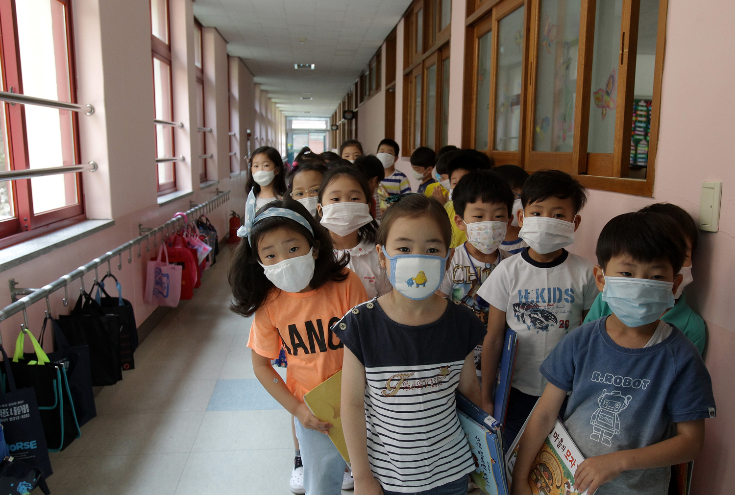 Elementary school students wear masks as a precaution against the MERS virus as they wait for a lesson to start at Midong Elementary School on June 9, 2015 in Seoul, South Korea.