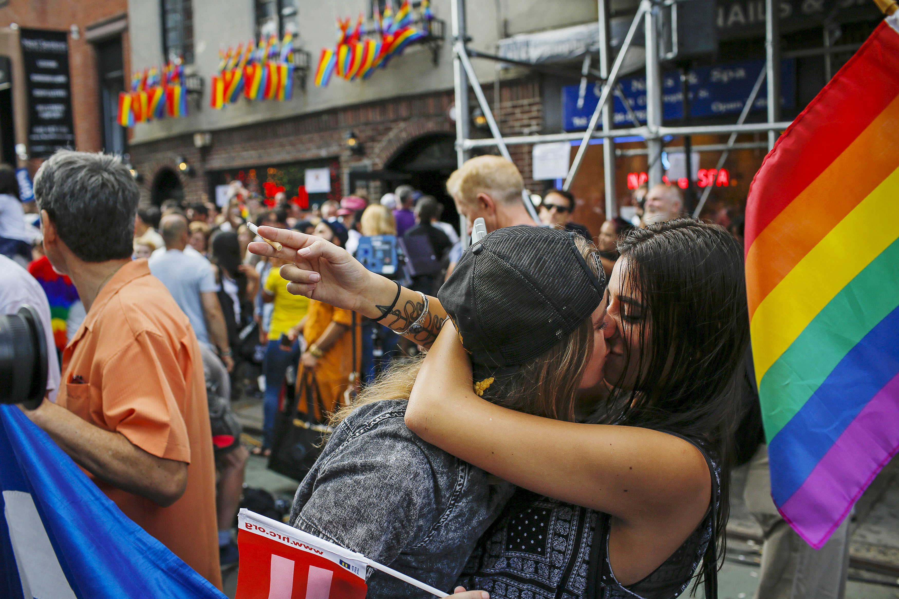 Women kiss each other as people celebrate outside the Stonewall Inn in the West Village neighborhood of New York June 26, 2015.