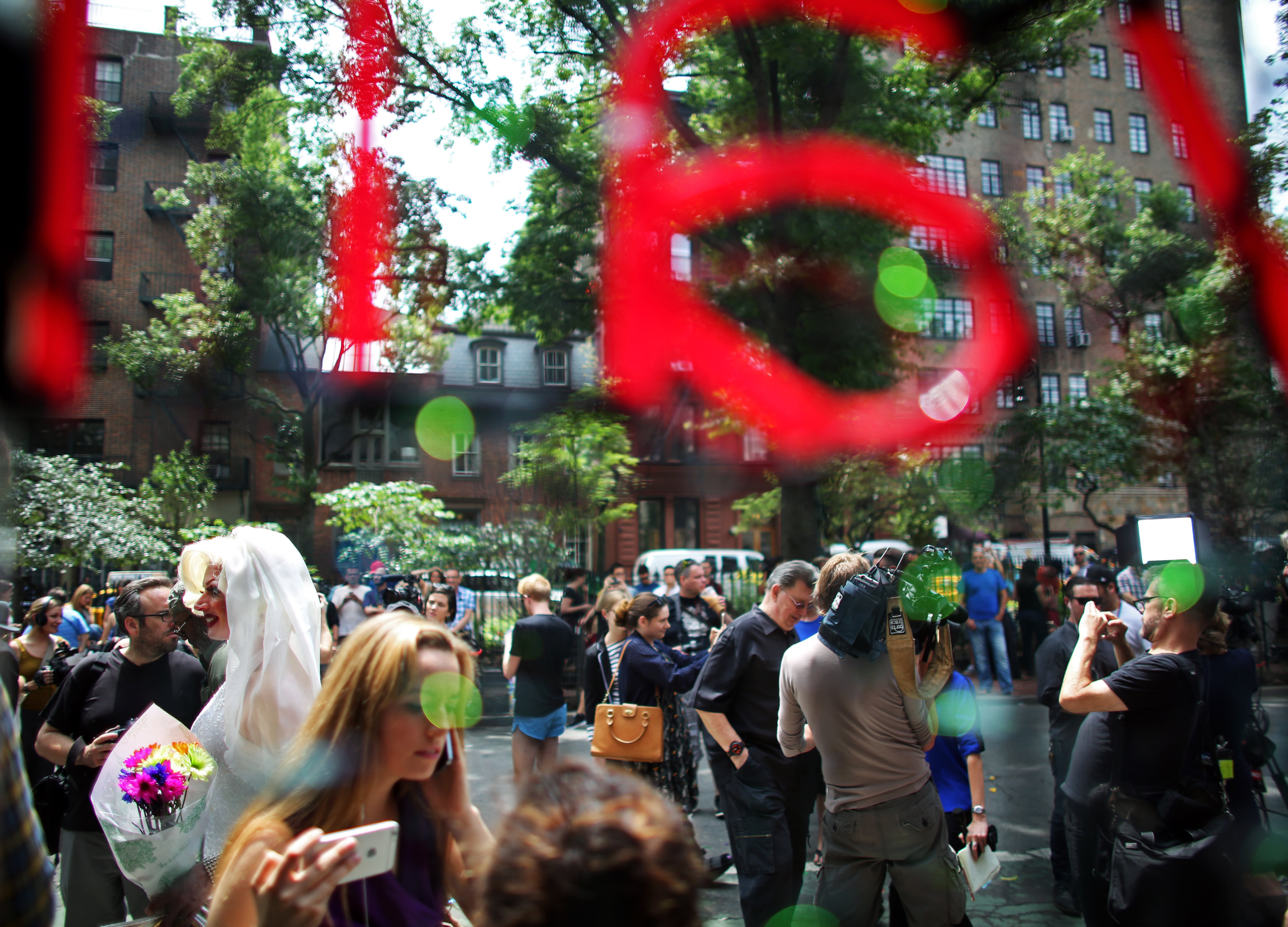 Carlotta Gurl (in wedding dress, left,) a gay rights activist from Vancouver, Canada, celebrates outside of the Stonewall Inn, an iconic gay bar recently granted historic landmark status, on June 26, 2015 in the West Village neighborhood in New York City.