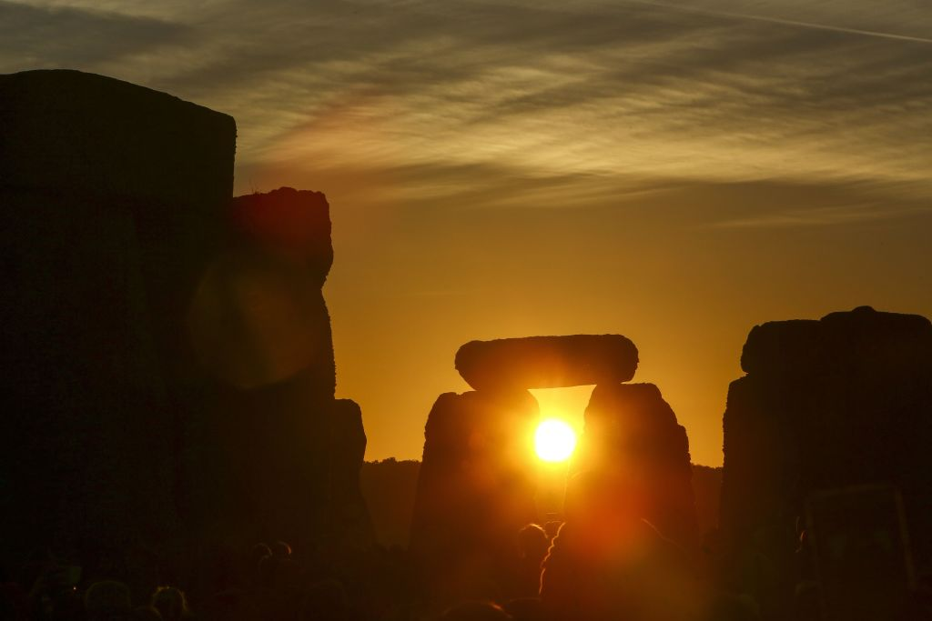 Revellers watch the sunrise as they celebrate the pagan festival of Summer Solstice at Stonehenge in Wiltshire, southern England on June 21, 2018.