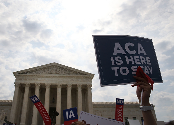 A sign is held up that reads  ACA Is Here To Stay  front of the US Supreme Court after ruling was announced in favor of the Affordable Care Act. June 25, 2015 in Washington, DC.