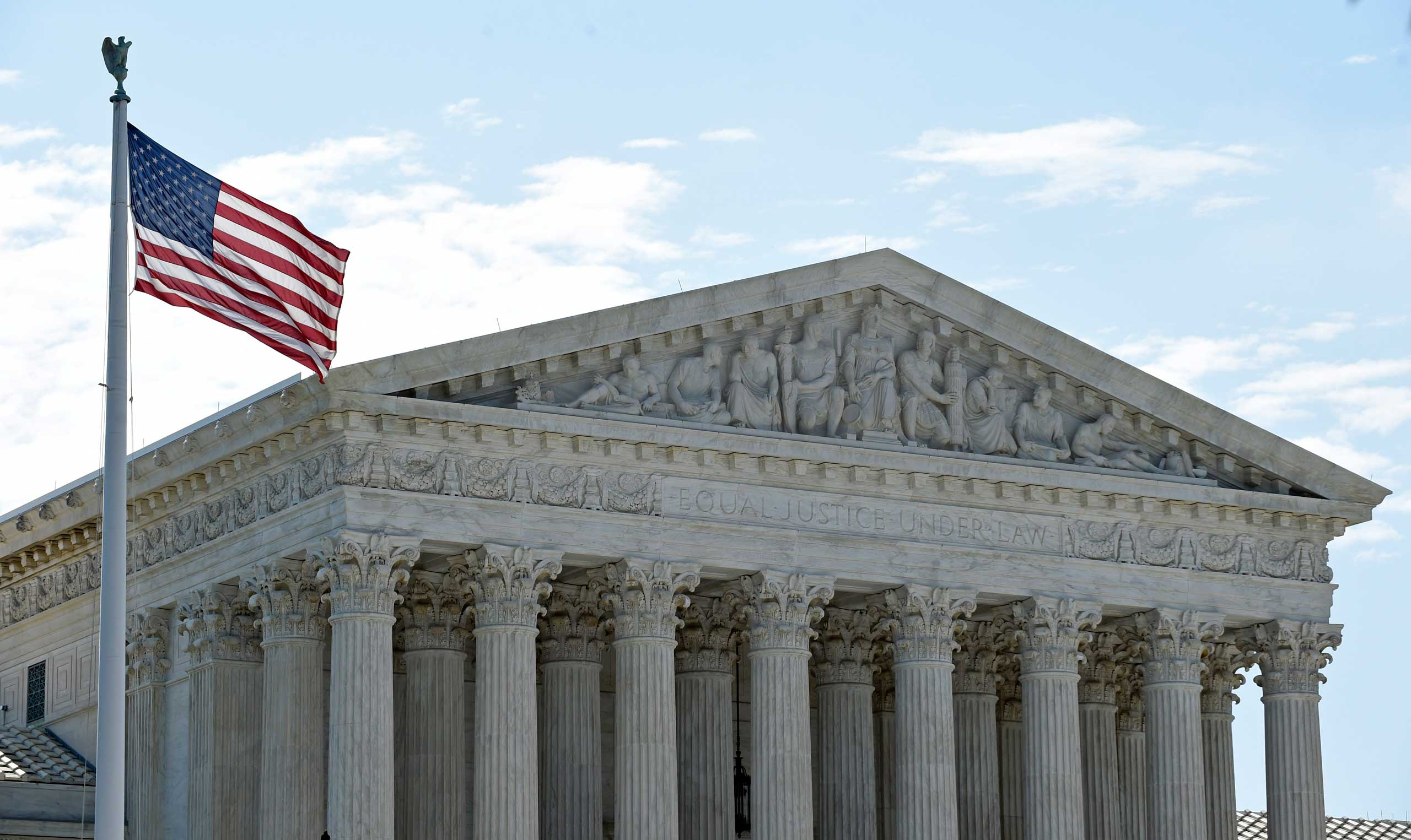 The American flag flies in the wind in front of the Supreme Court in Washington on June 22, 2015.