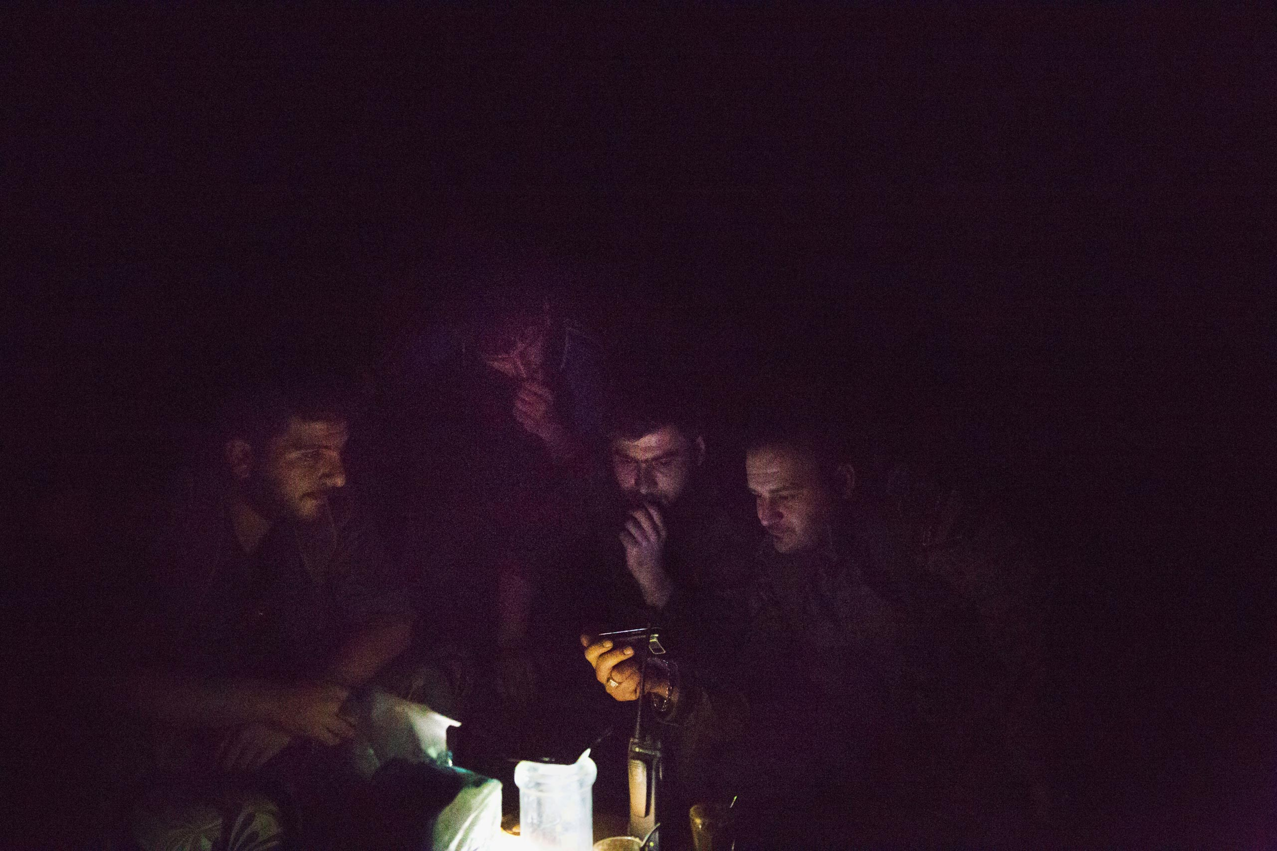Deep inside the industrial district of Deir-ez Zor, close to known ISIS positions, fighters with the Syrian government's Directorate of Military Intelligence watch a video on a cellphone, May 16, 2015.