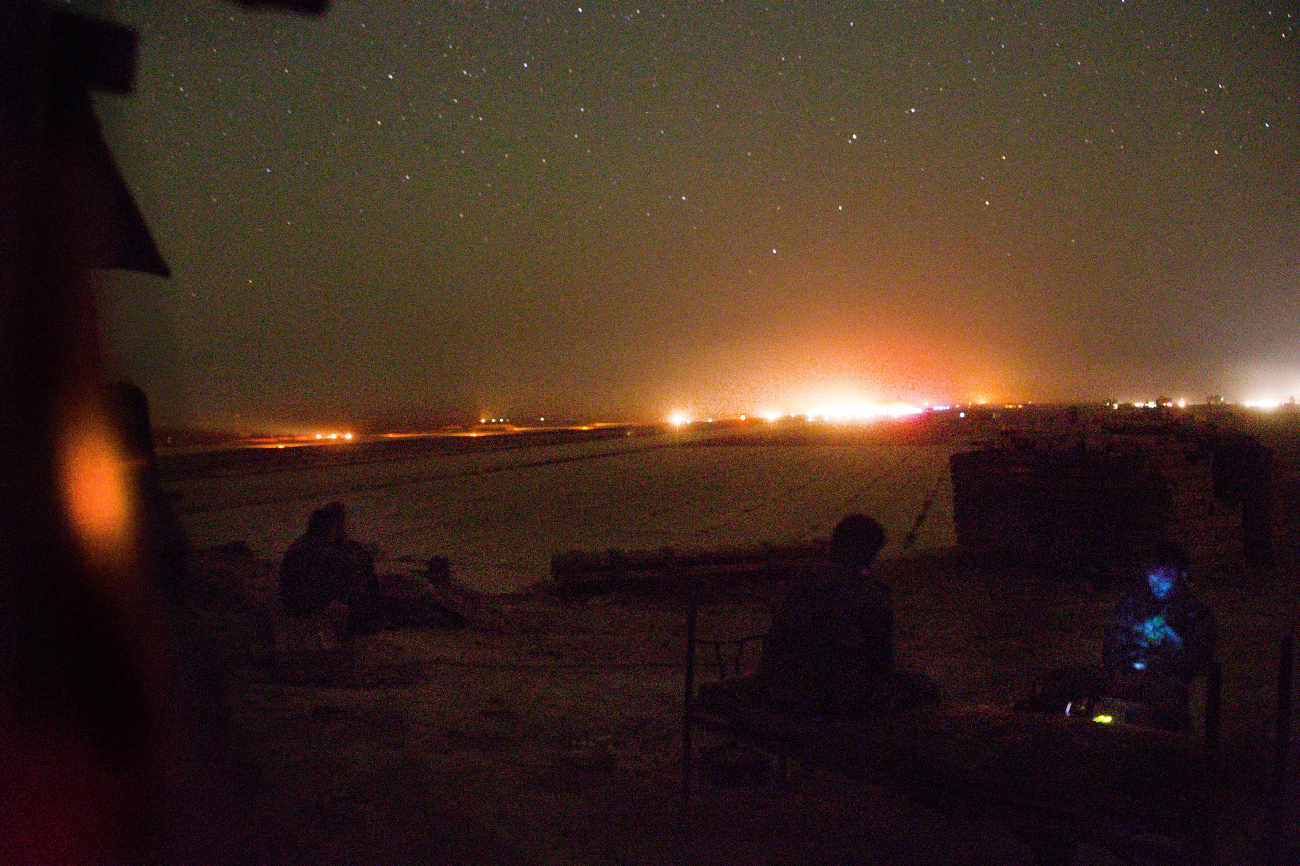 Syrian soldiers guarding the south-eastern front of the runway at Deir-ez Zor's airport watch as it lights up in preparation for a landing. Military flights that land at the base have become the only way in and out of the government-controlled parts of Deir ez-Zor. The nightly arrival of cargo planes transport munitions, food and medical supplies to the government held parts of the city, May 20, 2015.
