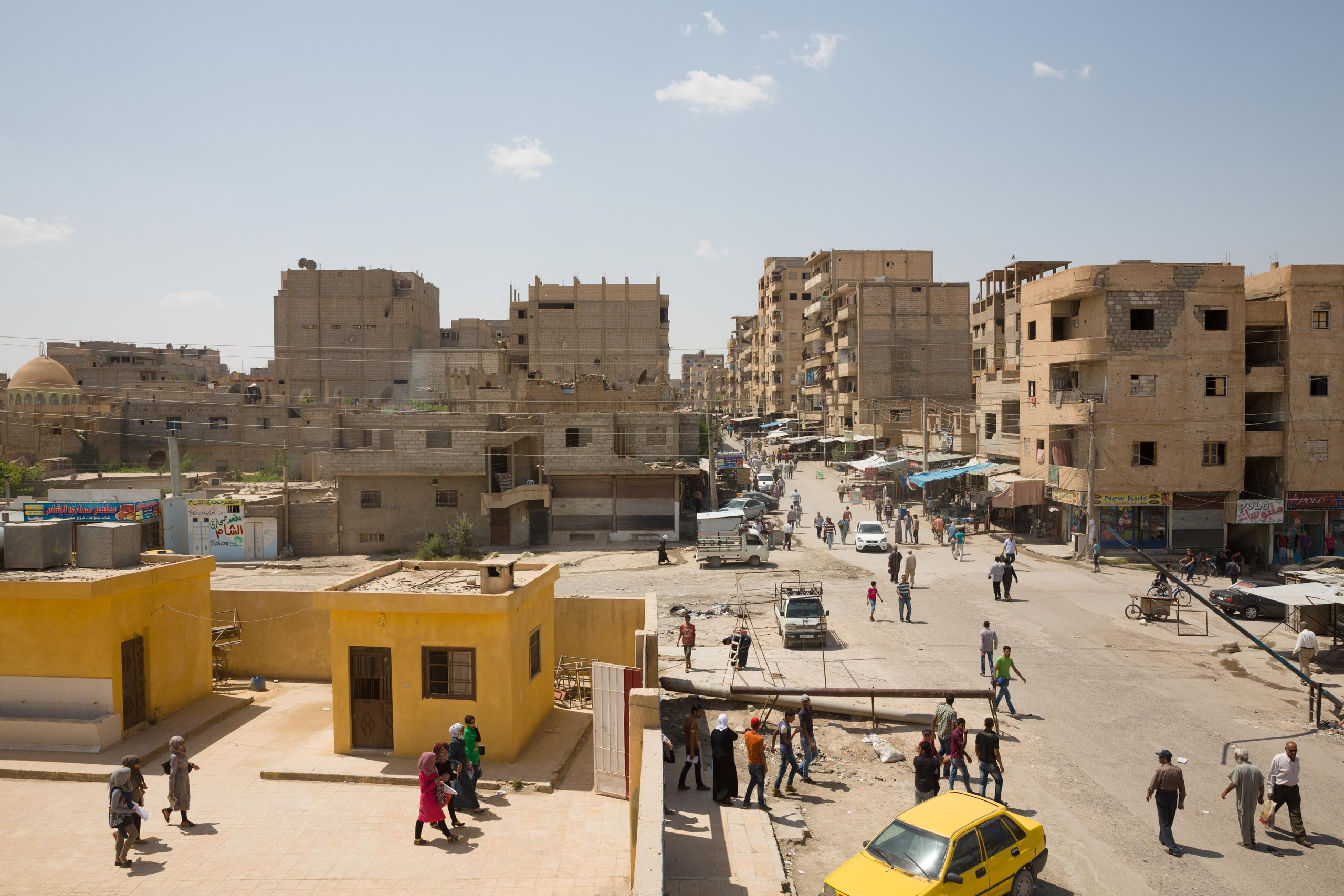 A view of the government-held section of Deir-ez Zor. The children on the left are leaving a school, which is still operating. In a siege that began in December 2014, ISIS fighters have encircled the city in Syria's eastern desert, May 24, 2015.