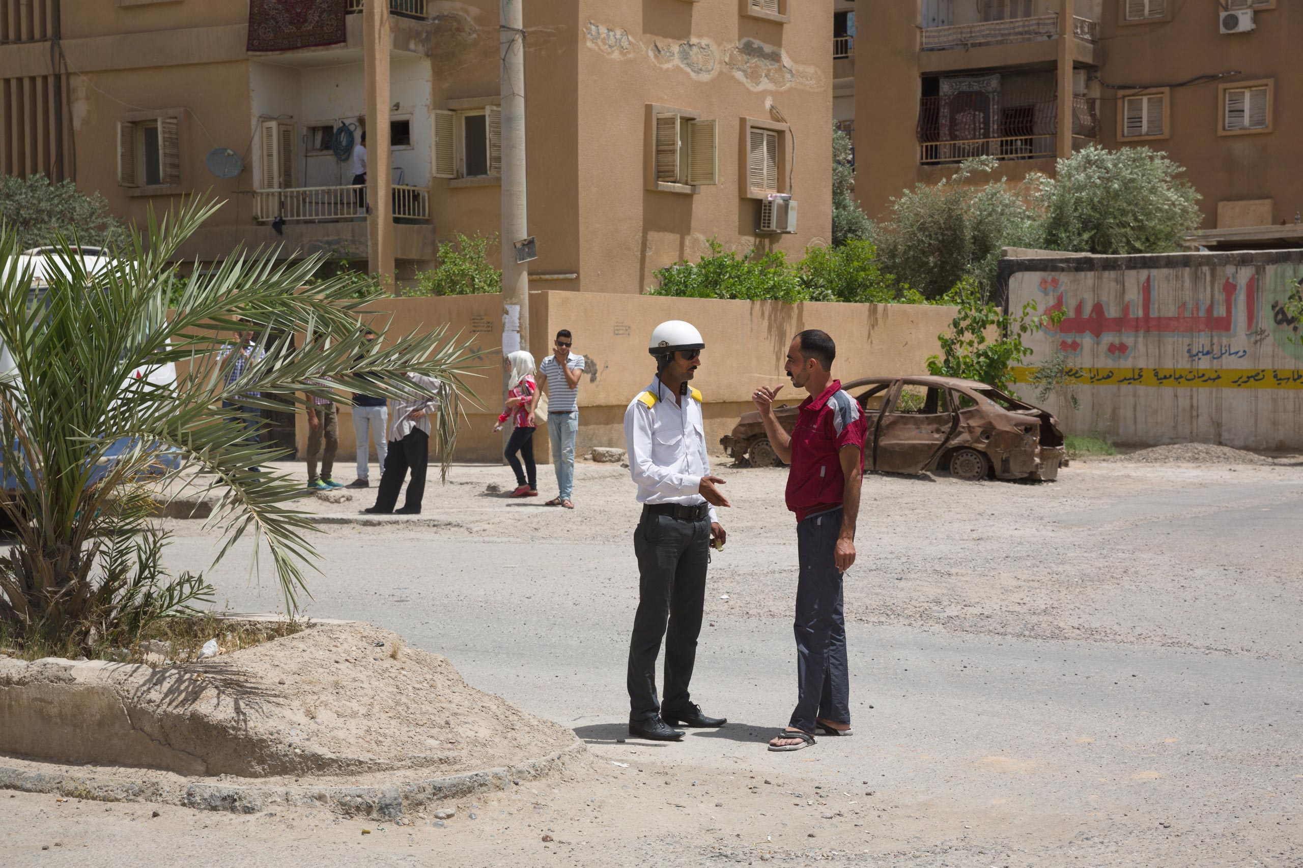 Traffic cops in black trousers, pressed white shirts and white helmets direct traffic on the mostly empty roads of Deir-ez Zor. Because of the ISIS blockade of the city, however, electricity and water have been cut off, and there is no fuel for cars, May 25, 2015.