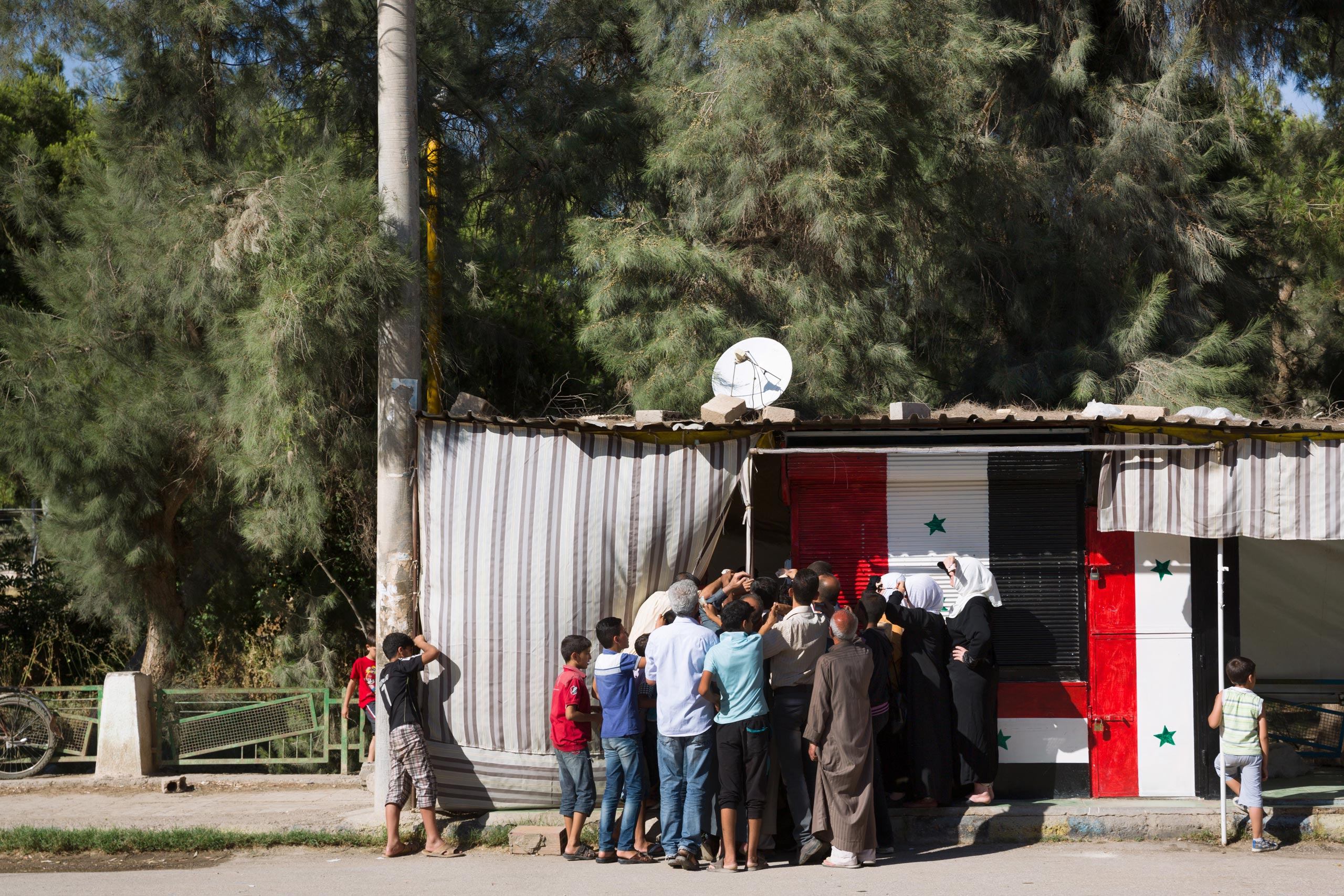 Residents often wait hours to buy bread provided by government-run bakeries because food is scarce. The Syrian government is struggling to retain normalcy in Deir-ez Zor, while fighting ISIS for control of the city, June 1, 2015.