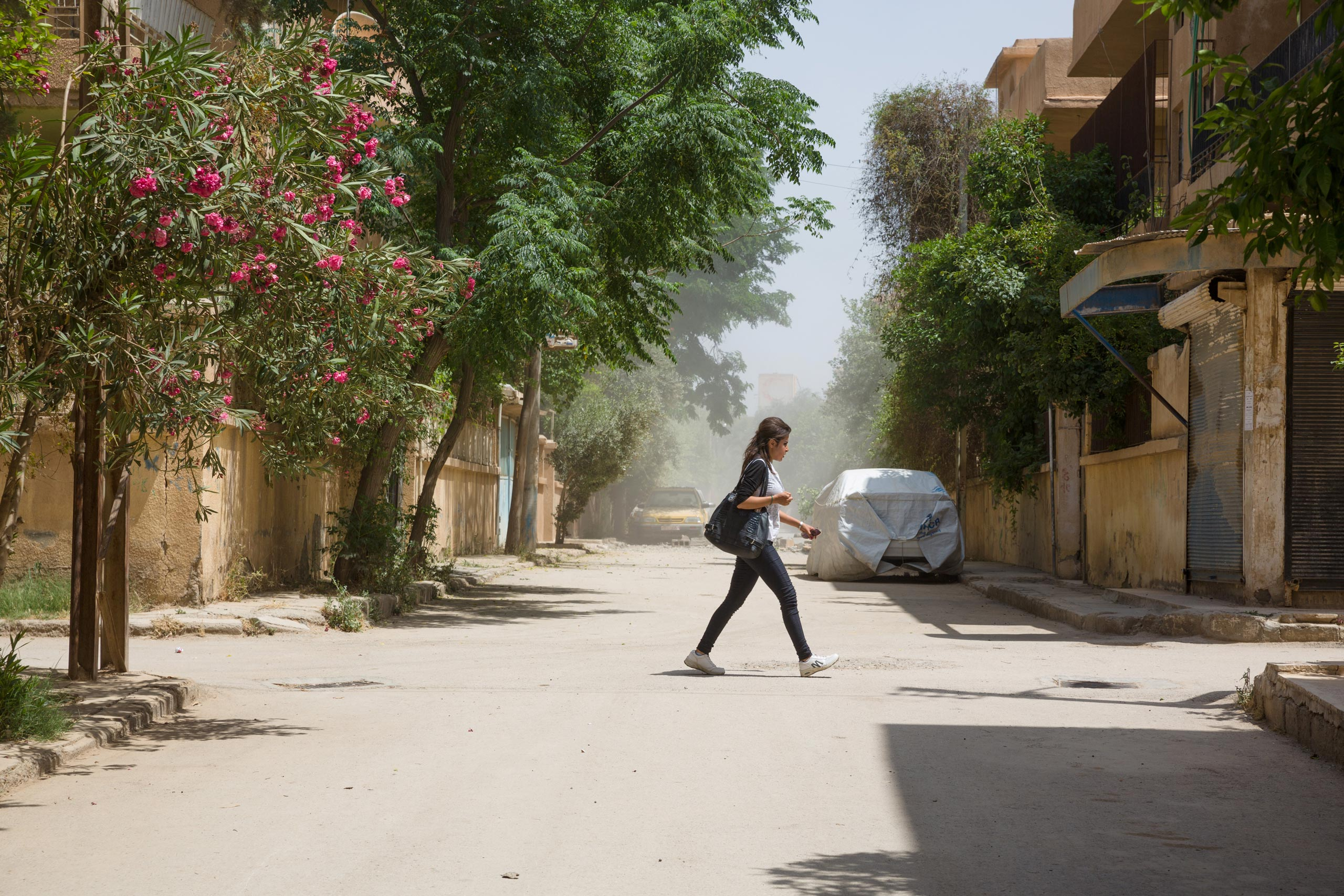 A young woman crosses a street in Ghazi Ayaash, a residential neighborhood of Deir-ez Zor a few hundred feet from the frontline, after a mortar attack from an ISIS position. The city is an outpost of modernity surrounded by ISIS-controlled areas where strict Islamic law is enforced, May 20, 2015.