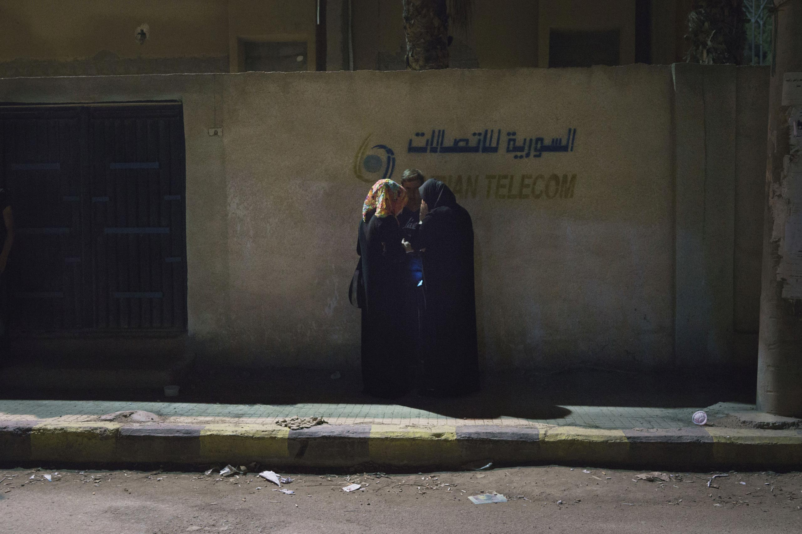 Residents of Deir-ez Zor huddle while trying to get a cell phone signal. Since the ISIS blockade of the city, electricity has been cut, making communication with the outside world difficult. Some cell towers, which are also used to provide internet service, now operate only three days a week, June 4, 2015.