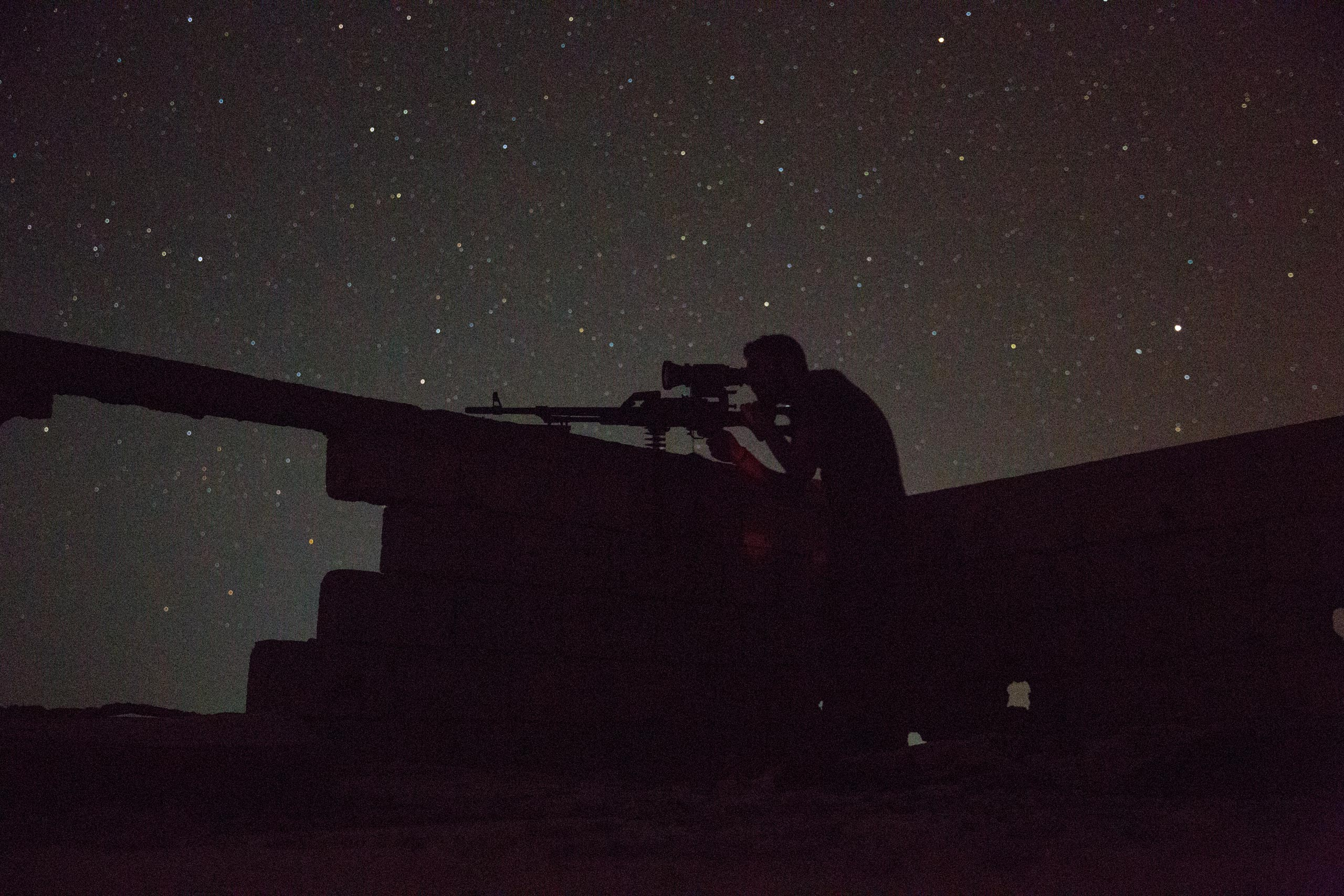 Jibril, a Christian fighter with the Syrian government's Directorate of Military Intelligence, surveys known ISIS positions using a night vision scope mounted on a Russian squad assault weapon, May 20, 2015.