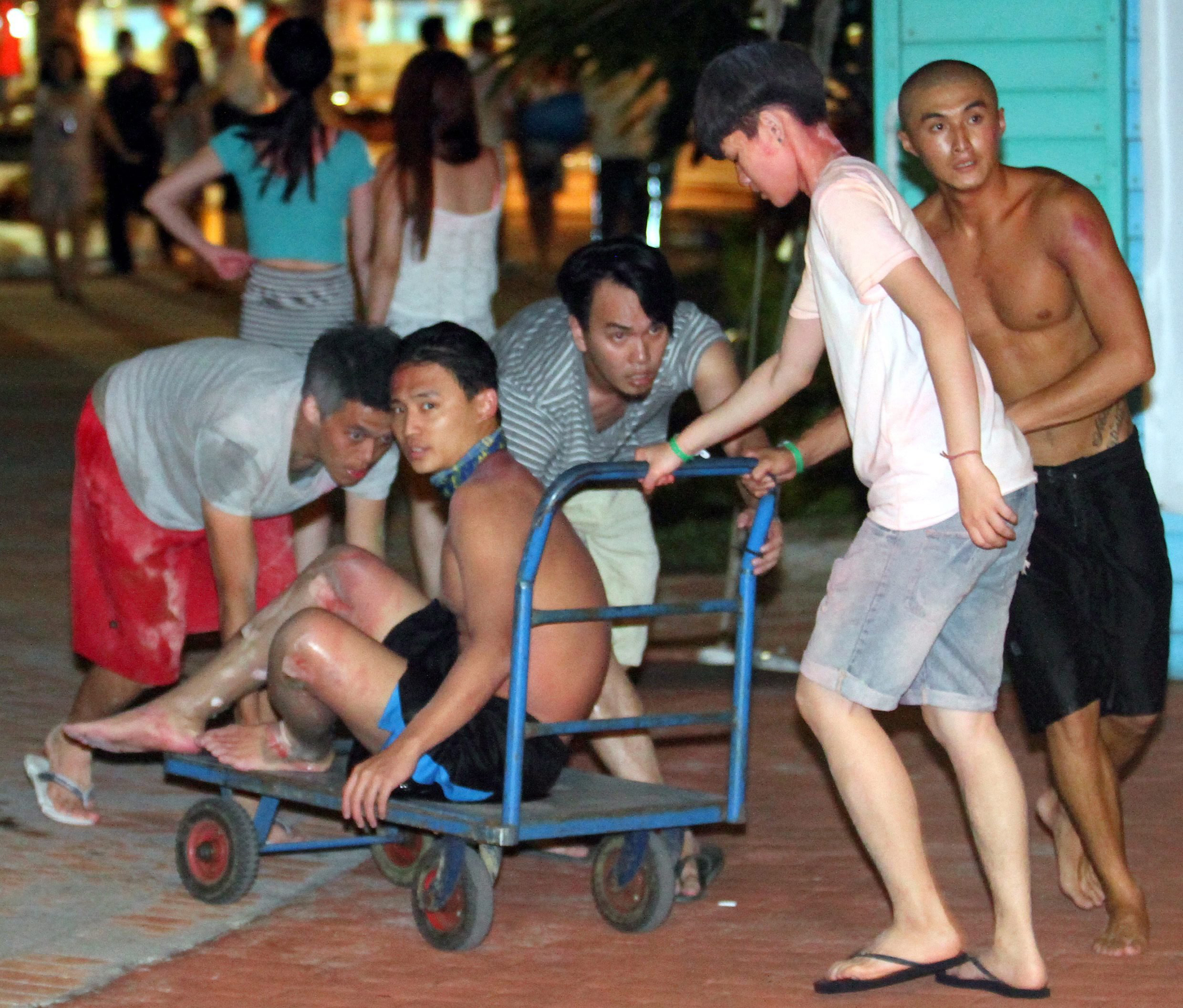 Taiwanese push a young man suffering from burns on his legs to an ambulance at the Formosa Fun Coast park in the Bali District of New Taipei City, northern Taiwan, June 27, 2015.