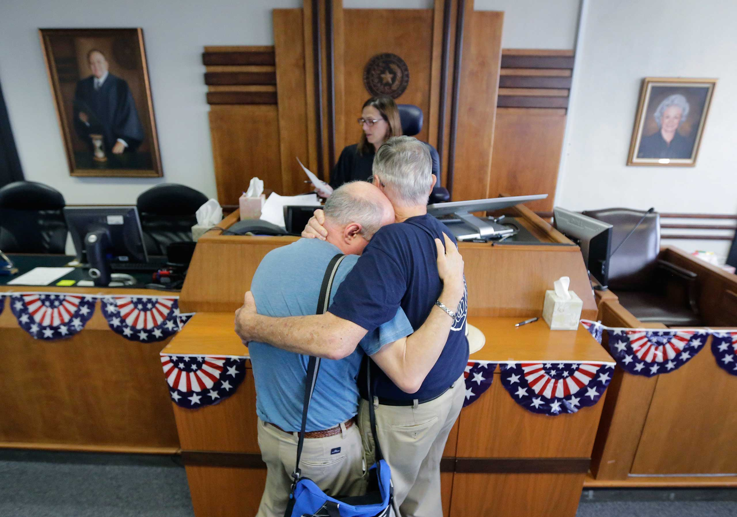 Gerald Gafford, right, comforts his partner of 28 years, Jeff Sralla, left, as they stand before Judge Amy Clark Meachum to receive a time waiver before marrying at the Travis County Courthouse in Austin, Texas on June 26, 2015.
