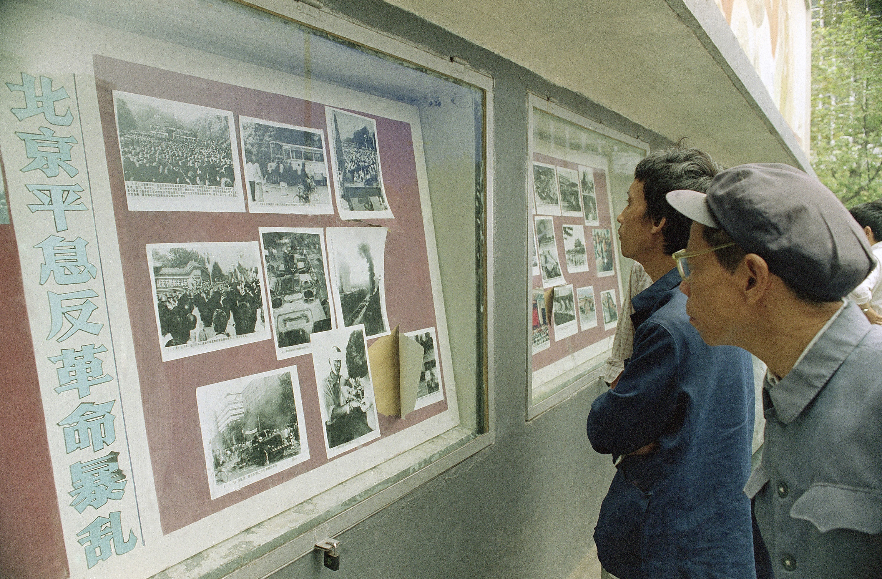 Viewers crowd around an official photo display in Chengdu, Sichuan province, China, on Oct. 30, 1989, that depicts violent battles there in June between police and a crowd angered by the Tiananmen Square killings in Beijing