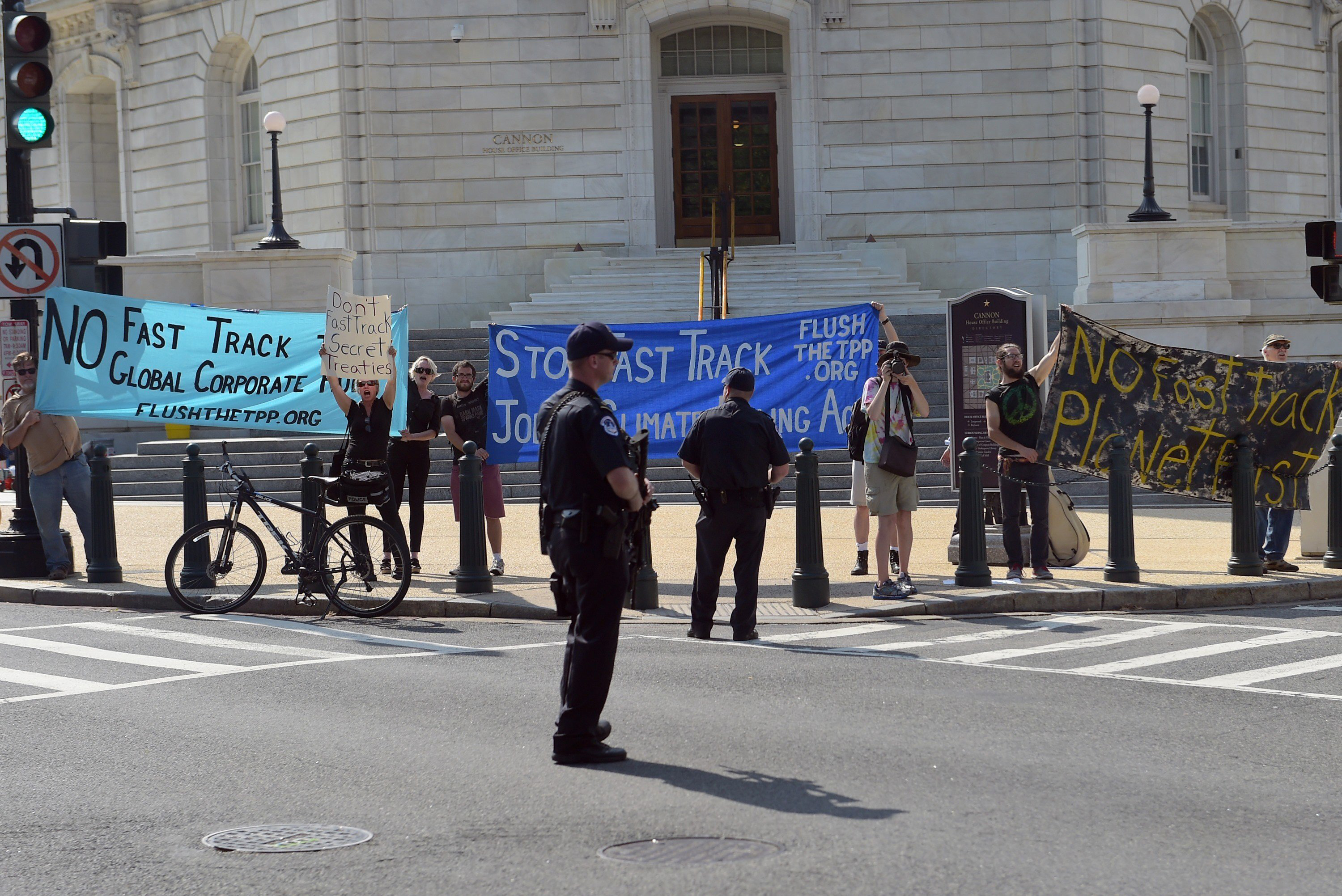 Anti-trade protestors hold banners outside of the Cannon House Office Building as US President Barack Obama arrived on Capitol Hill to lobby House Democrats on June 12, 2015 in Washington, DC.