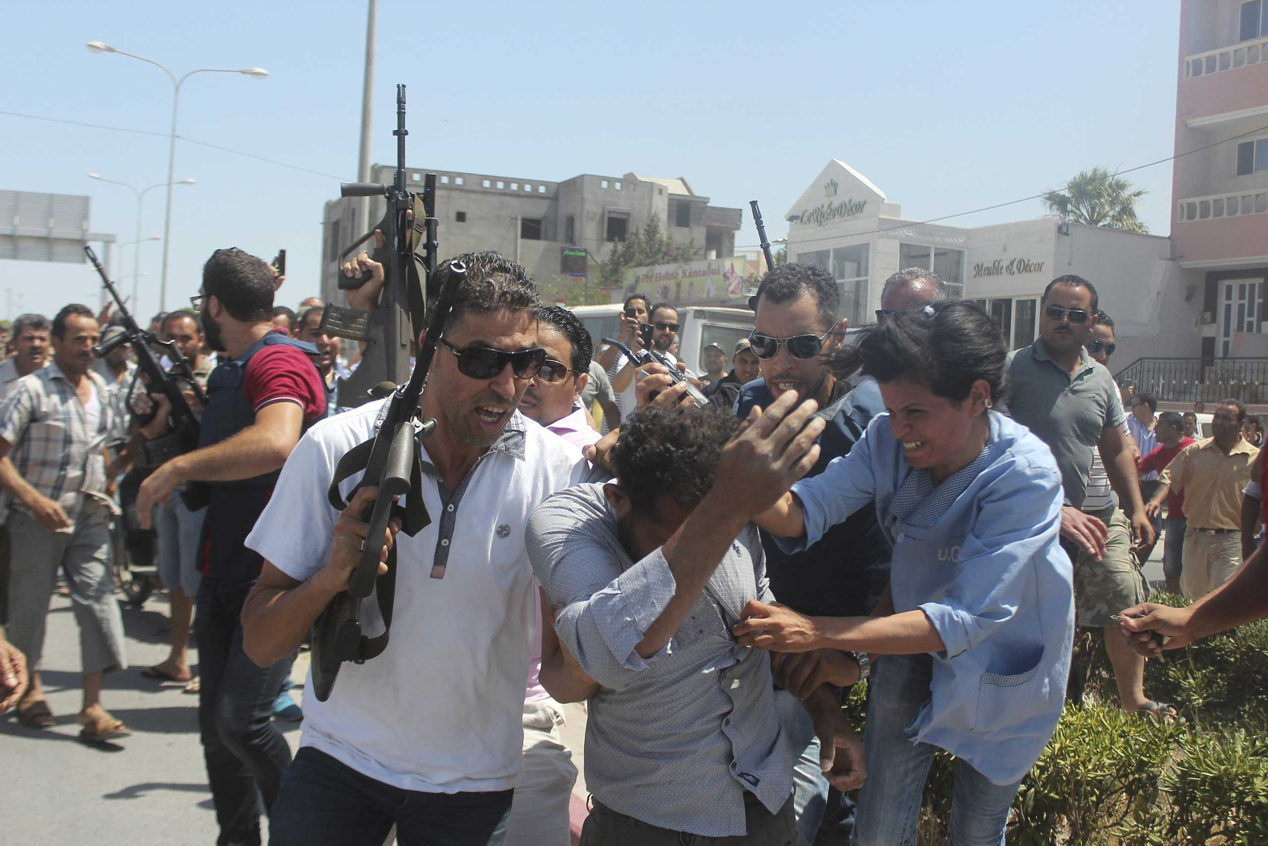 Police officers control the crowd, while surrounding a man suspected to be involved in opening fire on a beachside hotel in Sousse, Tunisia, as a woman reacts, on June 26, 2015.