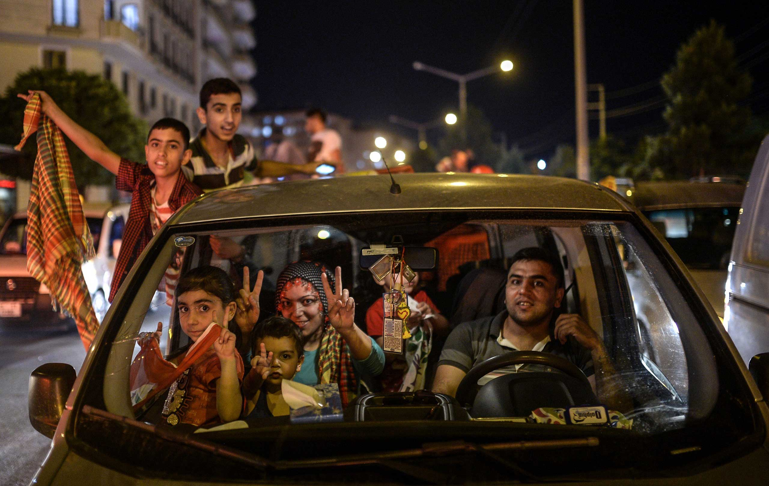 A family and children, supporters of pro-Kurdish Peoples' Democratic Party (HDP) celebrate the results of the legislative election, in Diyarbakir, Turkey, on June 7, 2015.