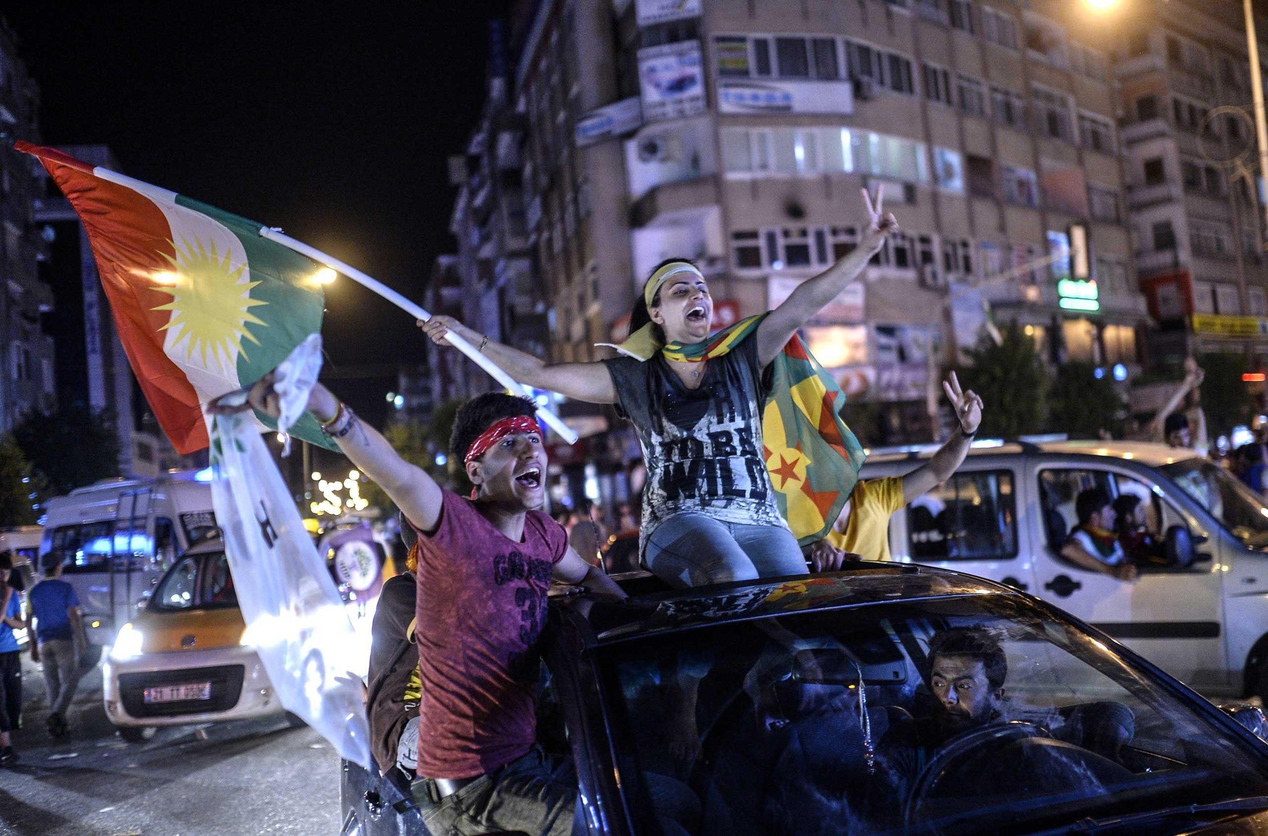 Young supporters of pro-Kurdish Peoples' Democratic Party (HDP) hold Kurdish flags as they celebrate the results of the legislative election, in Diyarbakir in Turkey on June 7, 2015.