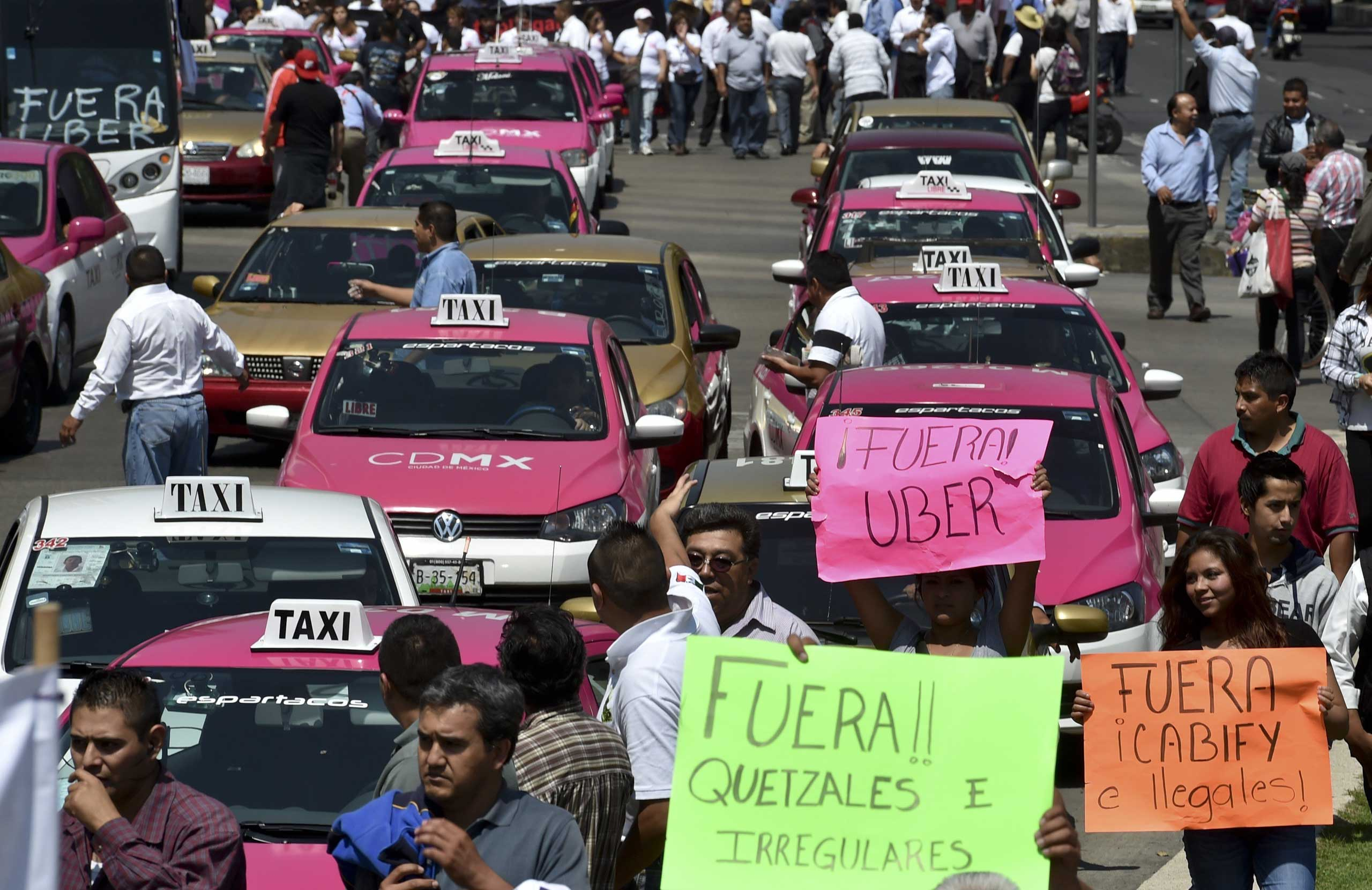 Taxi drivers take part in a protest against the private taxi company Uber for alleged unfair competition, in Mexico City on May 25, 2015.