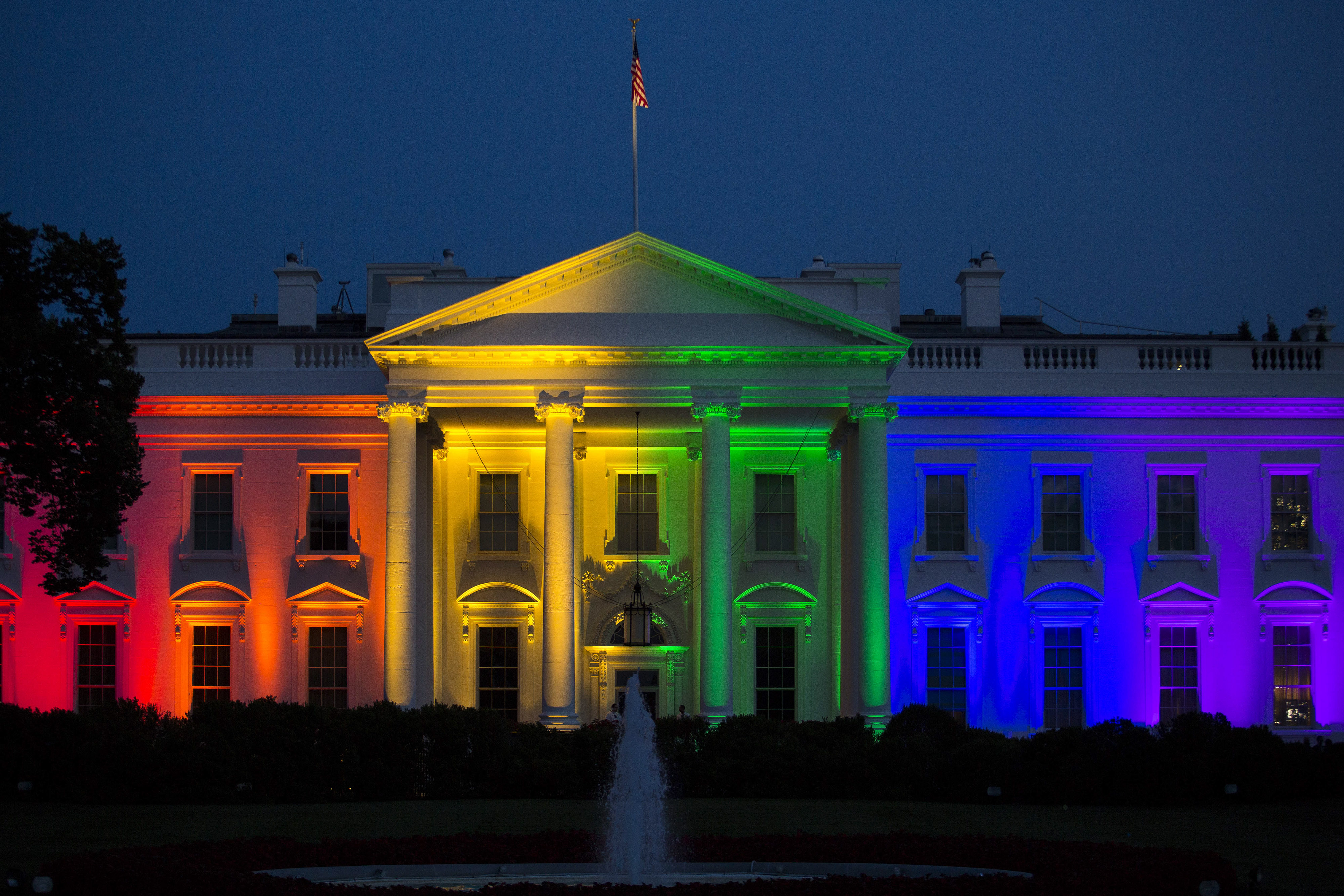 The White House stands illuminated in rainbow colored light at dusk in Washington, D.C., U.S., on Friday, June 26, 2015.