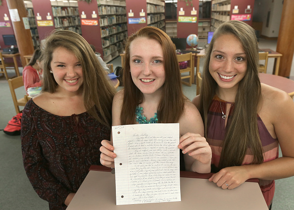 Apponequet Regional High School students, Mollykate Rodenbush, Brittany Tainsh, and Michaela Arguin (from left), hold the handwritten reply from Whitey Bulger.