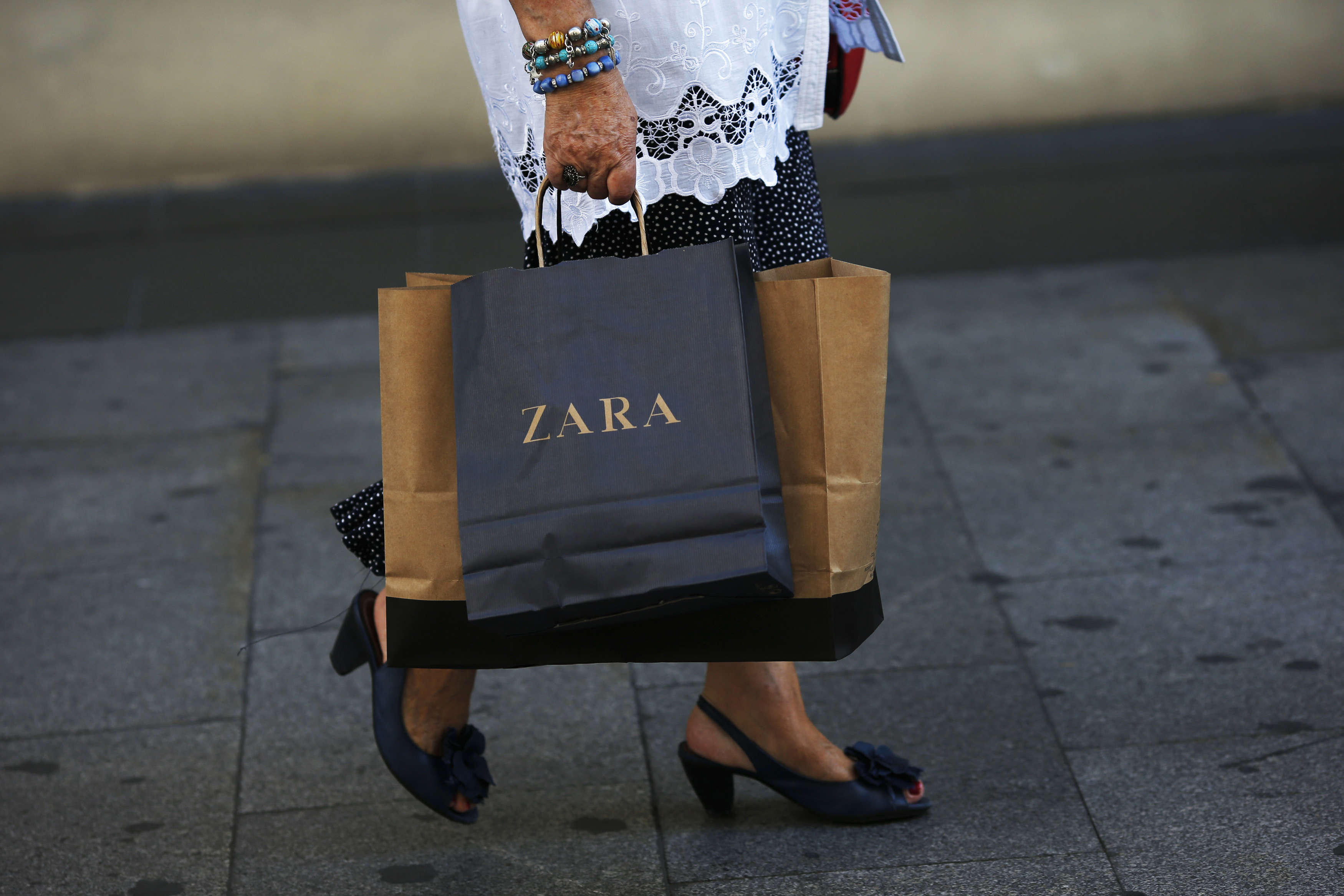 A woman walks with a Zara bag in hand in Madrid, September 19, 2012.