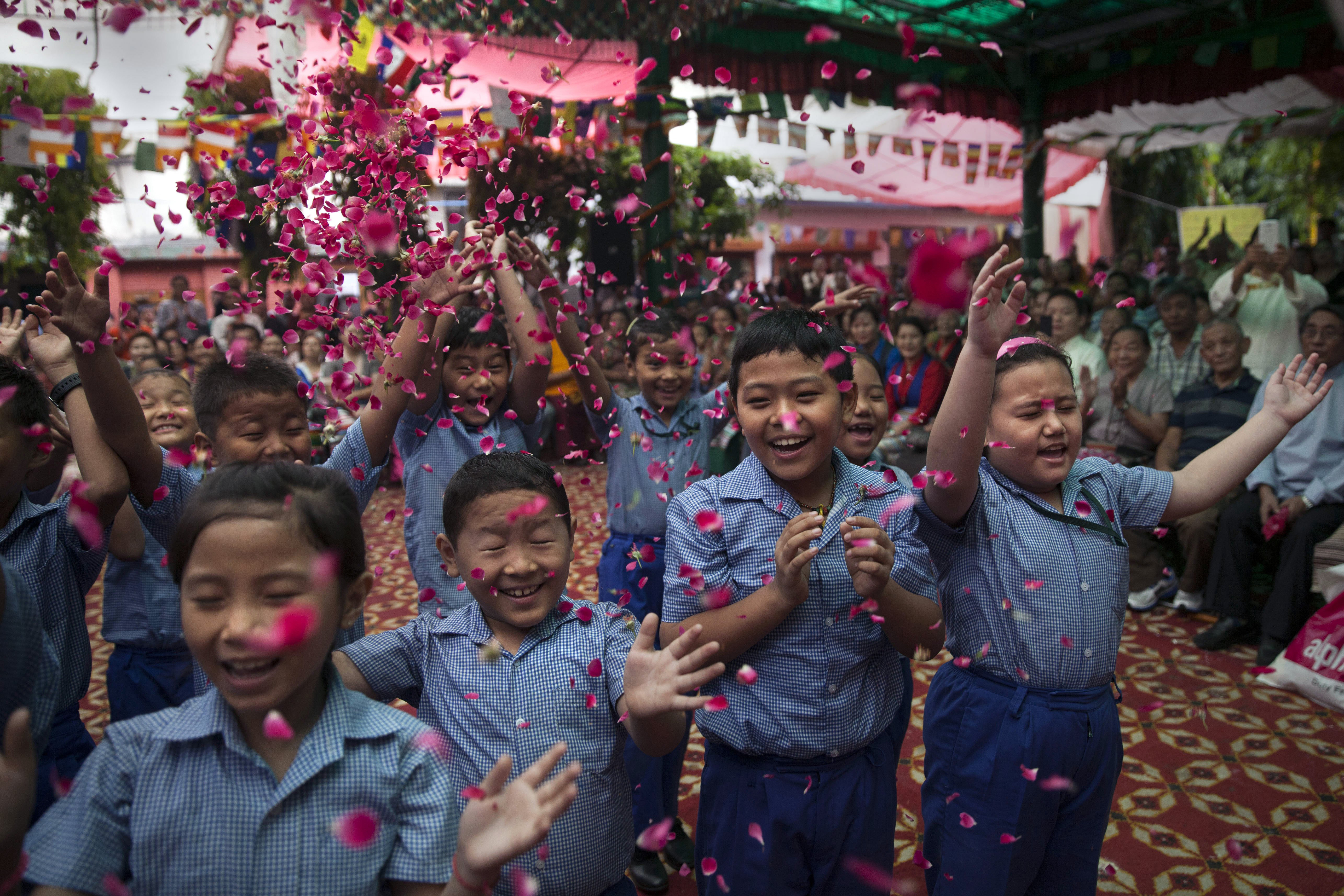Exiled Tibetan school children throw flowers in the air as they sing a birthday song to celebrate the Dalai Lama's 80th birthday in New Delhi, India on July 6, 2015.