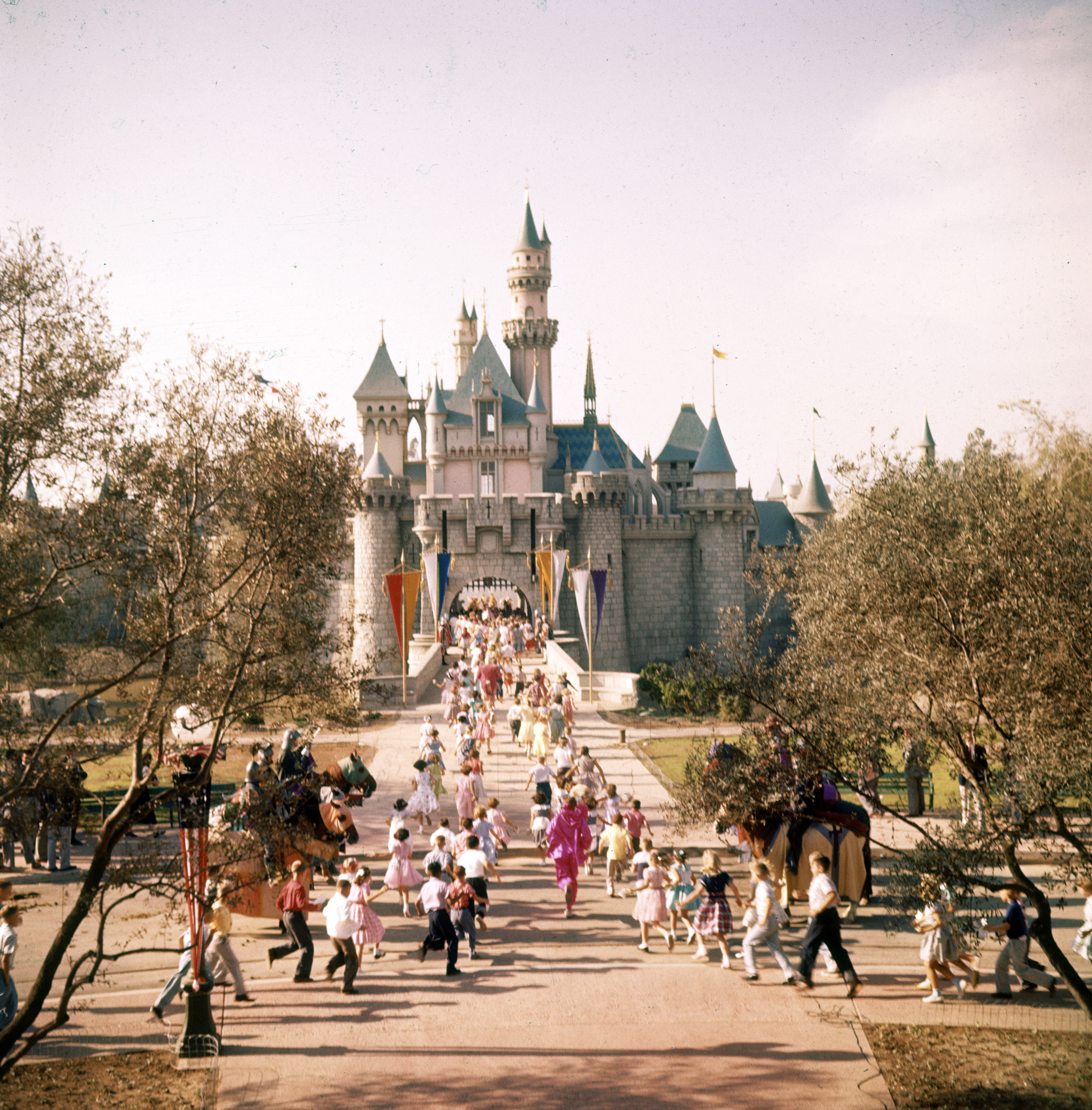 Caption from LIFE. Sleeping Beauty's castle in Fantasyland is overrun by children crossing drawbridge over moat. Inside, Disney plans a model torture chamber.