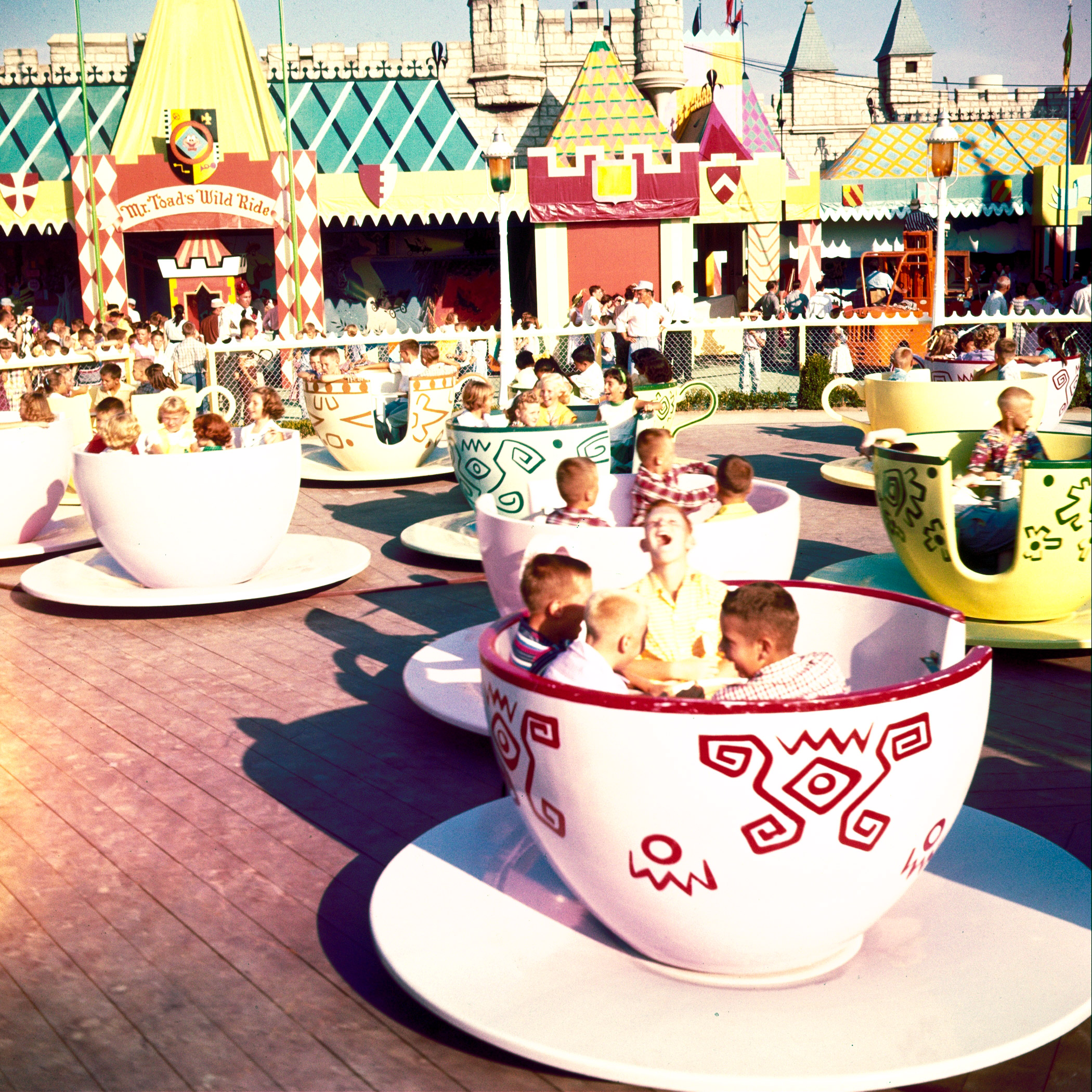 Caption from LIFE. Cups and saucers filled with squealing children as paying guests whirl through park's Fantasyland at Disney's  Mad Hatter's Tea Party.