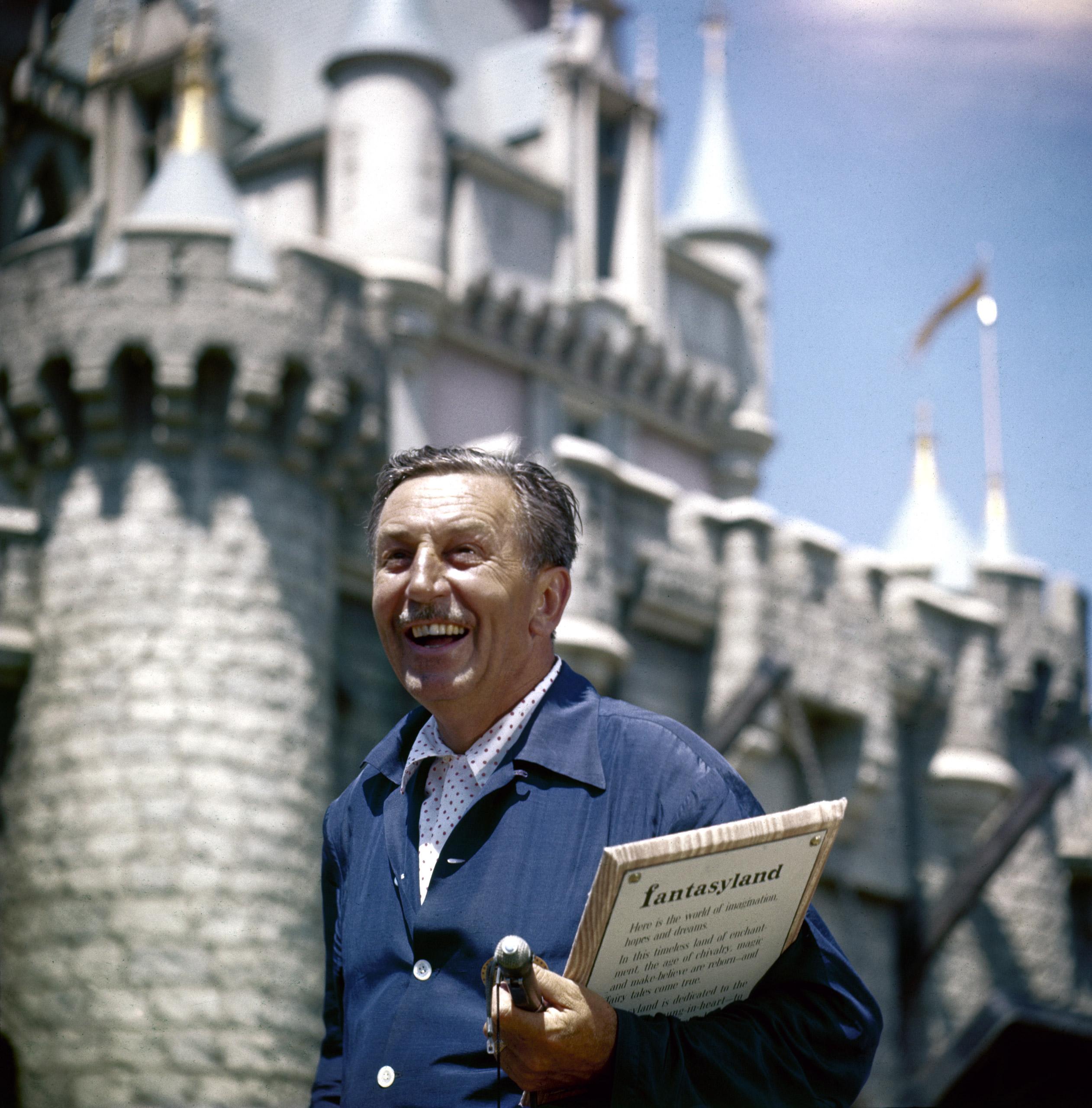 Walt Disney standing in front of Fantasyland Castle at Disneyland.