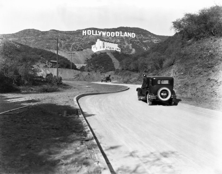 A sign advertises the opening of the Hollywoodland housing development in the hills on Mulholland Drive overlooking Los Angeles, Hollywood, circa 1924.