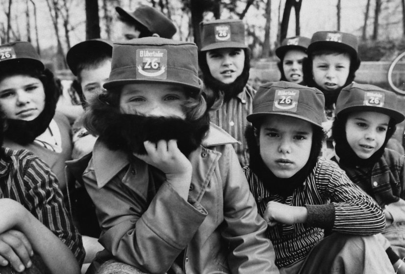 Children wearing Fidel Castro beards and hats, playing in the woods in 1959.