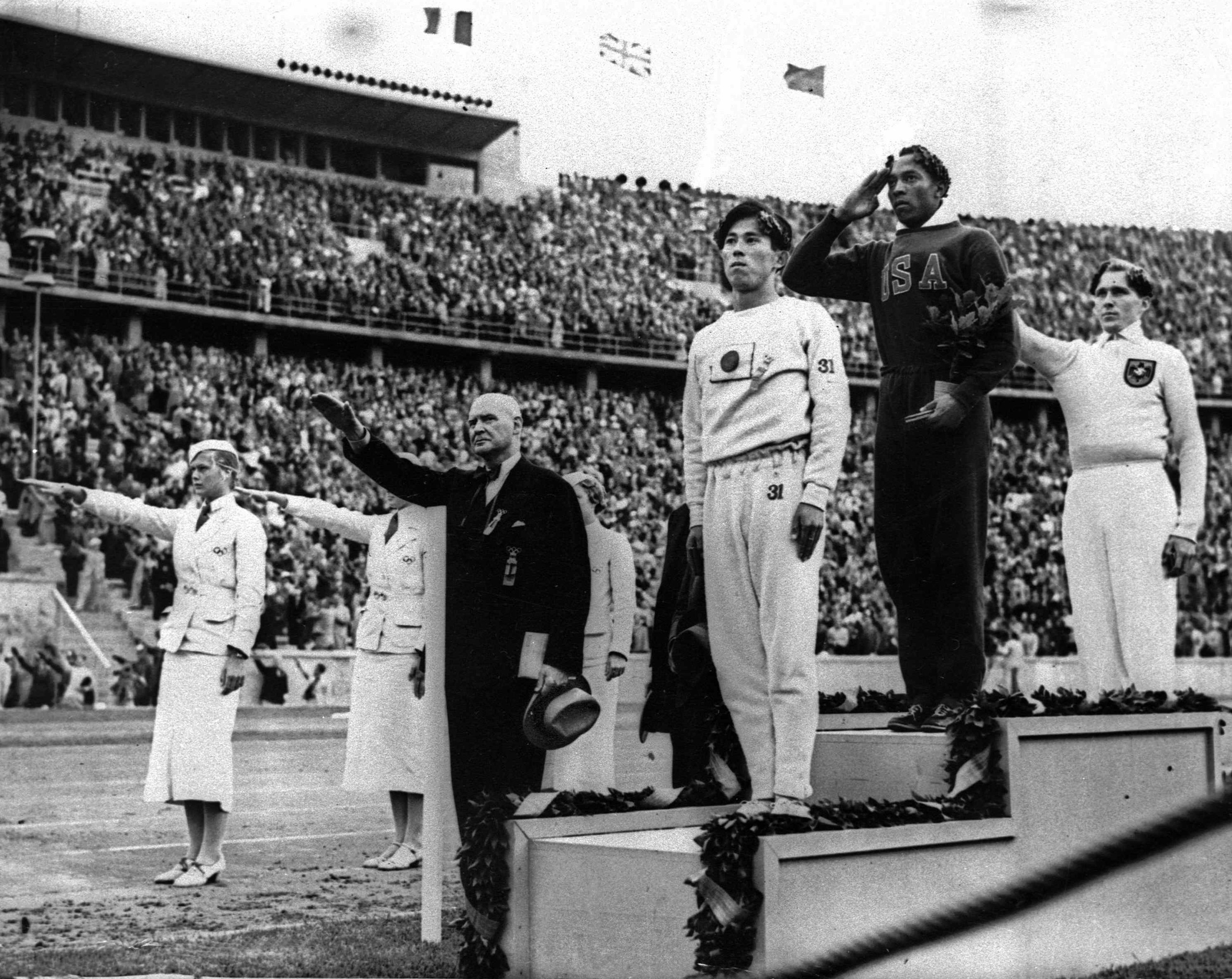 Olympic broad jump medalists salute during the medals ceremony at the Summer Olympics in Berlin. From left on podium are: bronze medalist Jajima of Japan, gold medalist Jesse Owens of the United States and silver medalist Lutz Long of Germany. Aug. 11, 1936.