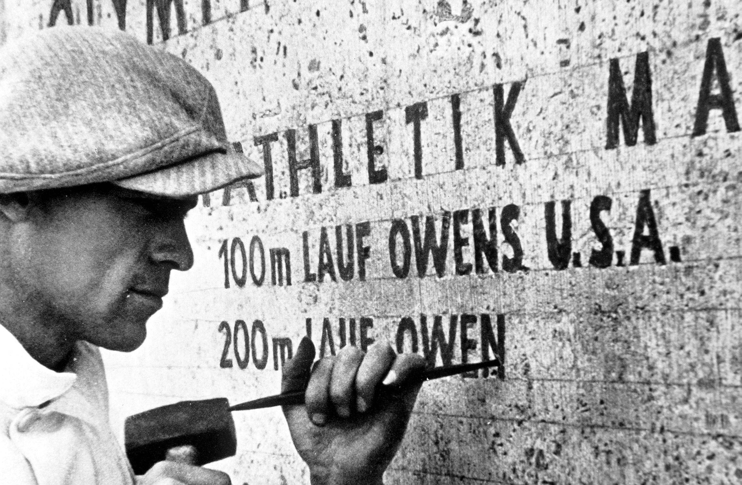 A stonemason at work records the feat of USA's Jesse Owens, winner of four gold medals in the Games, in 1936 in Berlin