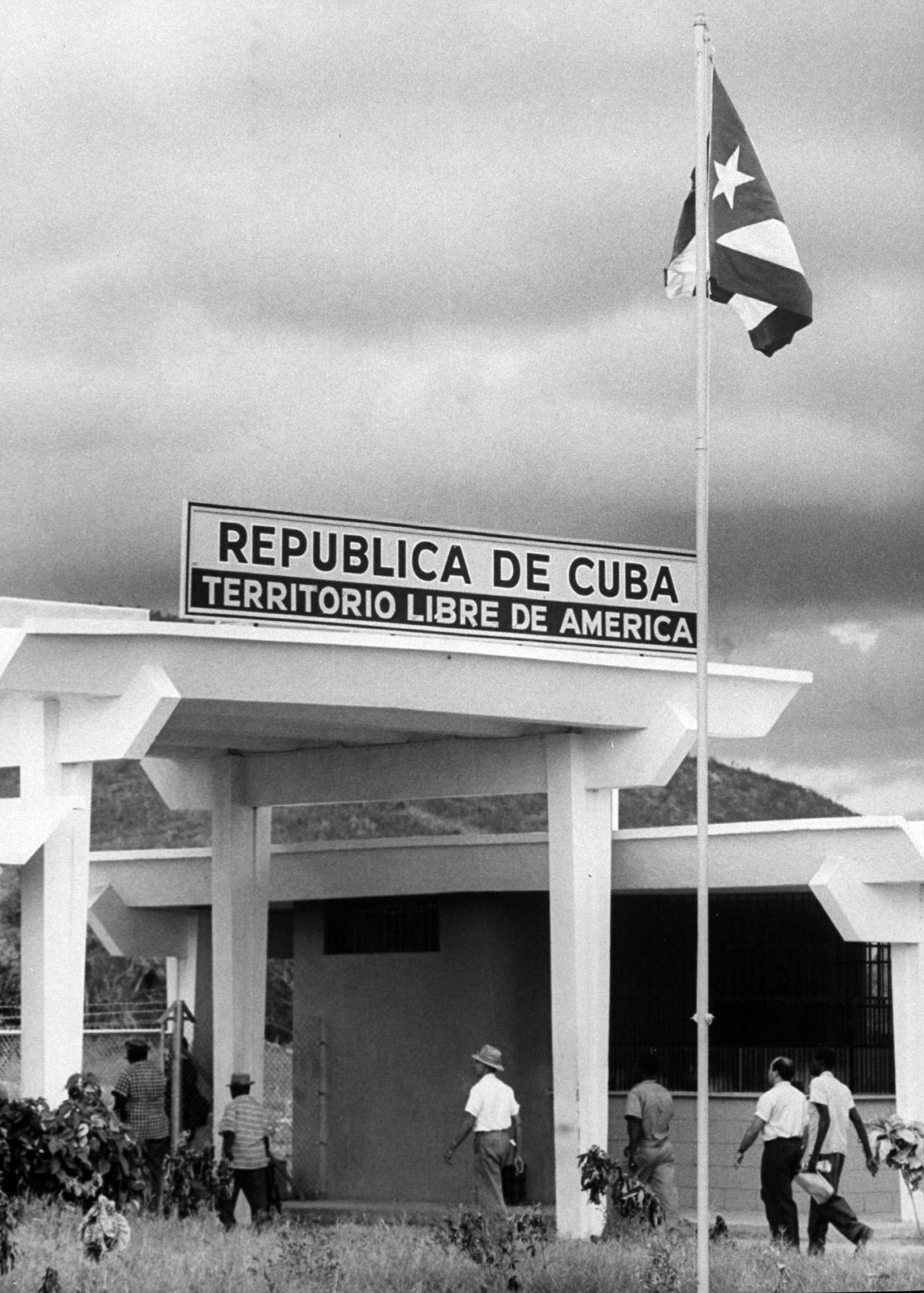 Cuban flag flying over Cuban border post set up at edge of American Naval Base of Guantanamo Bay.