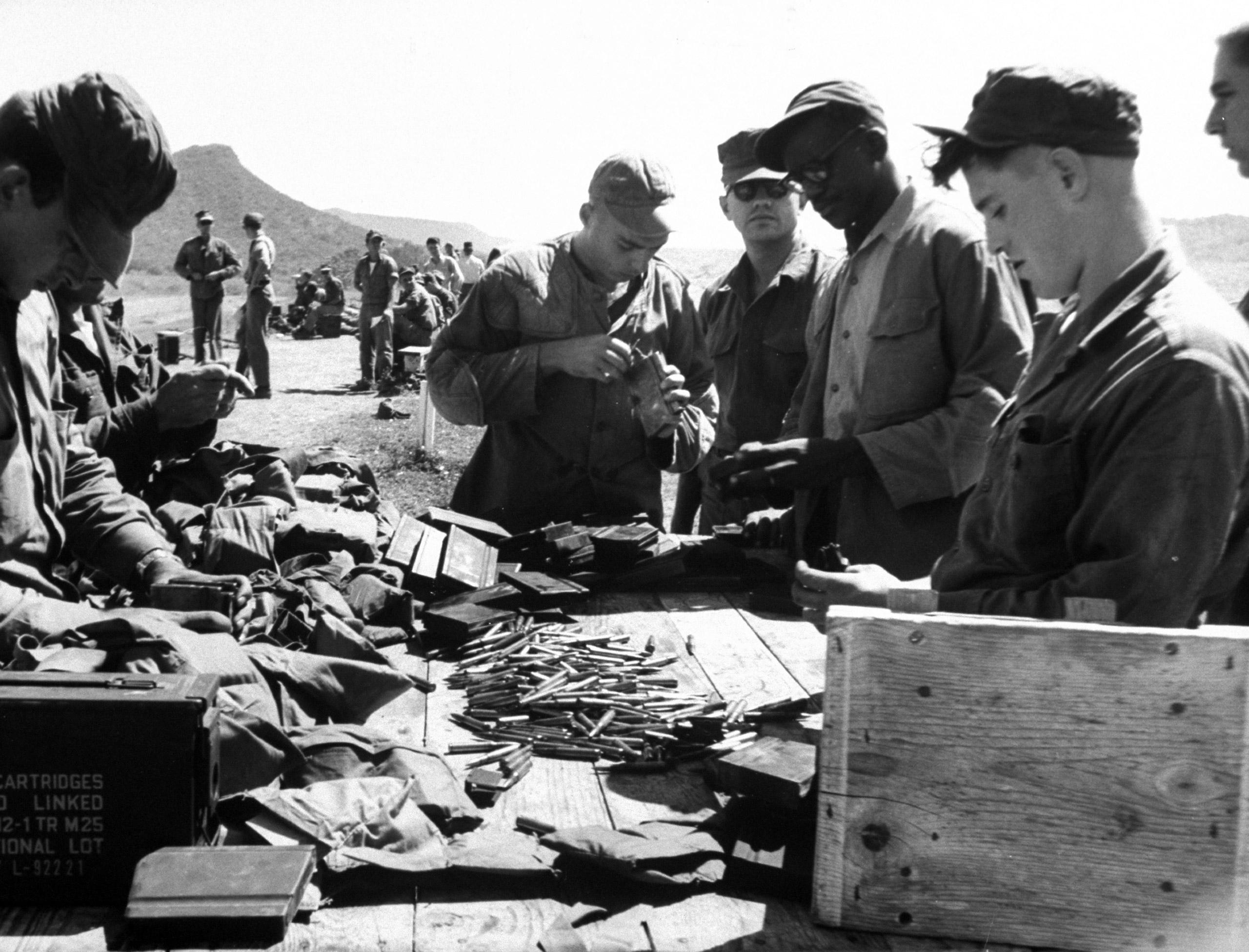 Ammunition shells being loaded into clips by sailors at Guantanamo Naval Base, Guantanamo Bay, Cuba, 1962.