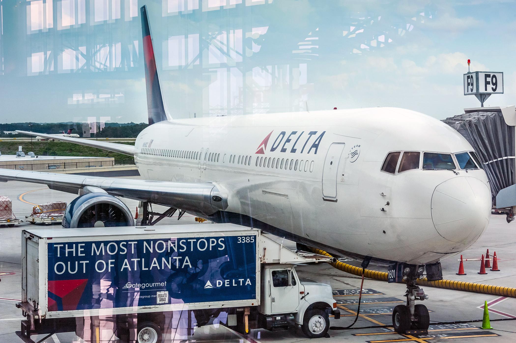 Delta Airlines passenger jet and service truck at Atlanta International Airport .