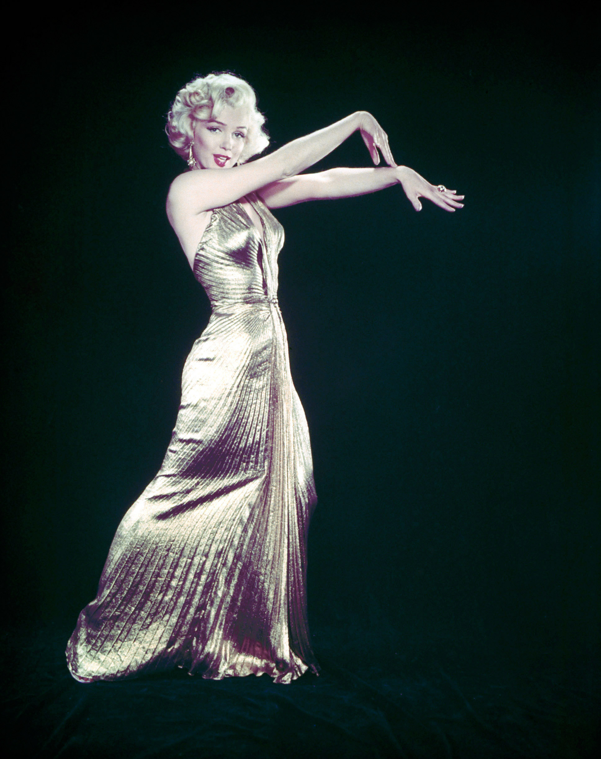 "Marilyn Monroe wearing her famous gold lamé gown designed by Bill Travilla for a publicity still for the motion picture ""Gentlemen Prefer Blondes,"" 1953."