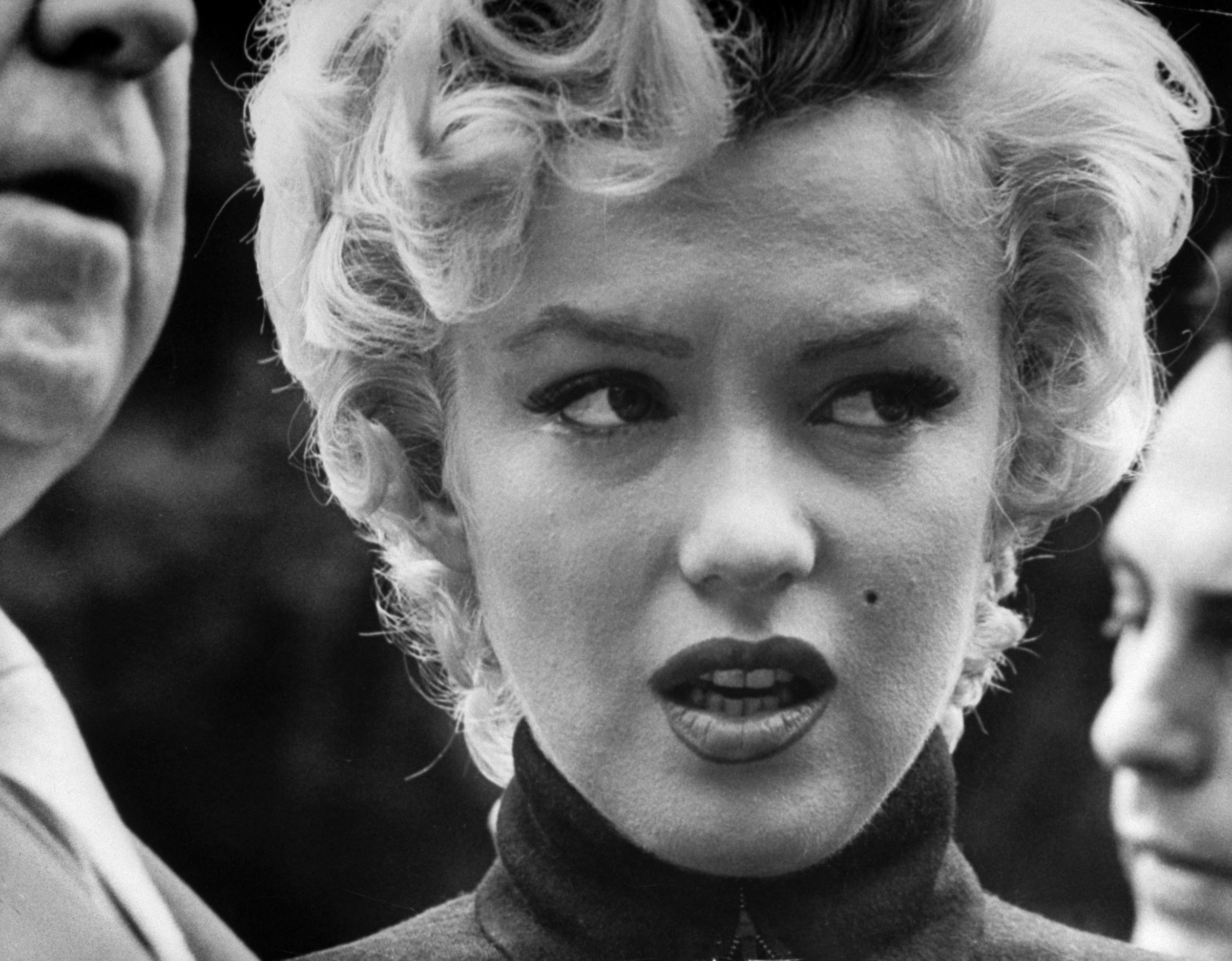 A tearful Marilyn Monroe standing outside her home to face dozens of reporters after the announcement of her divorce from Joe DiMaggio, 1954.