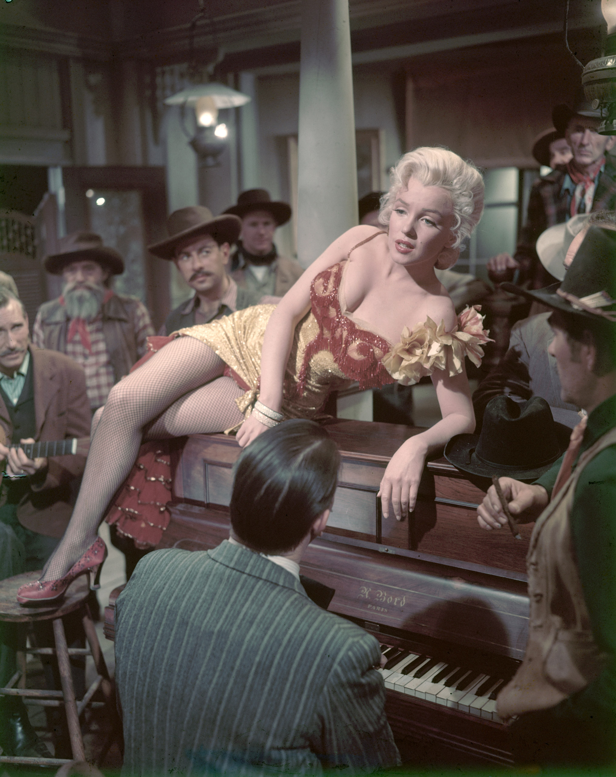 "Marilyn Monroe sits on a piano in a scene from ""River of No Return,"" 1954."