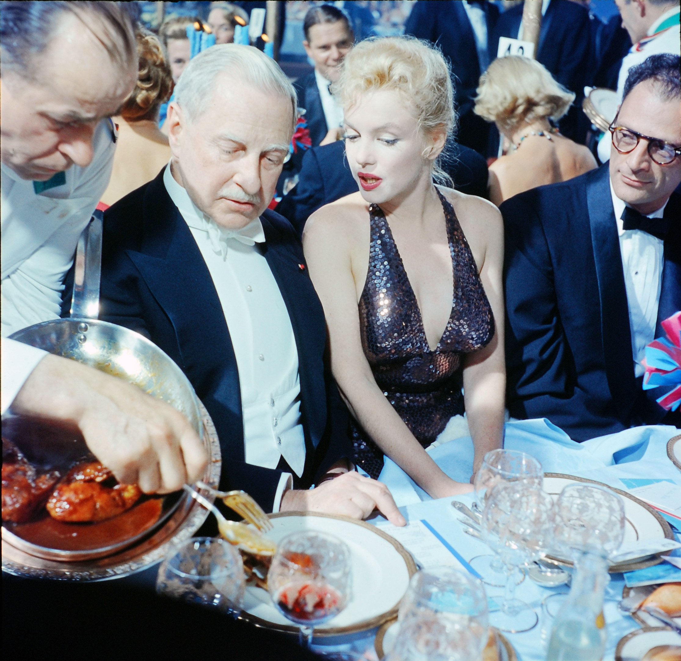 Ambassador Winthrop Aldrich, ex-envoy to Britain, chats with Marilyn Monroe as her husband, Arthur Miller, looks on at the April in Paris Ball, Waldorf Astoria Hotel, 1957.