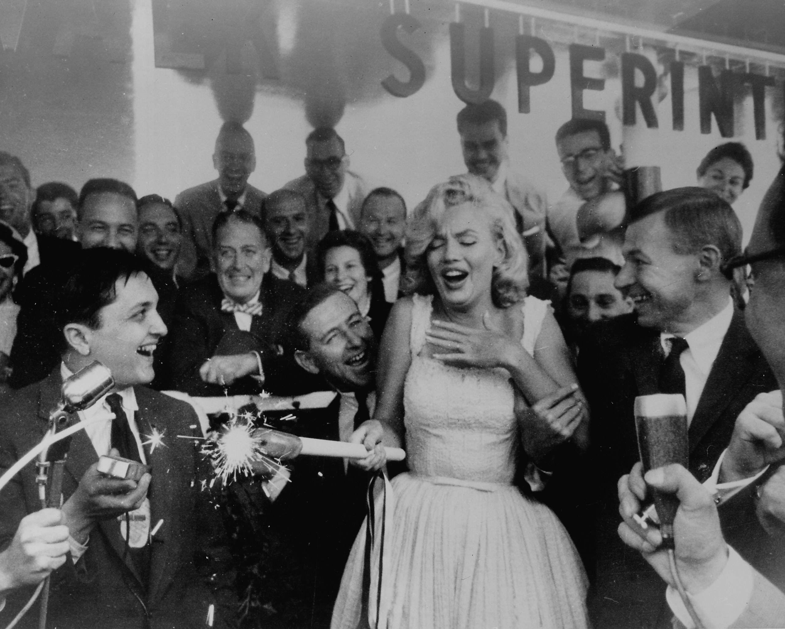 Marilyn Monroe looks startled while holding a flaming sparkler in the Rockefeller Center Sidewalk Superintendents Club during a ceremony for the soon-to-be built Time & Life Building, 1957.